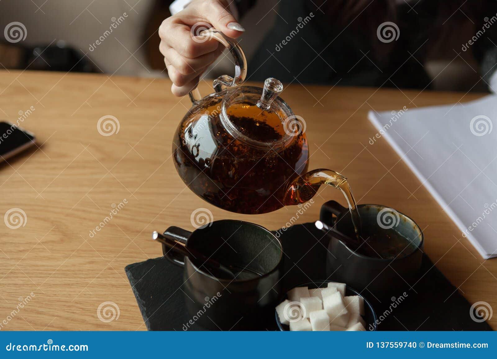 De bedrijfsdame geeft zwarte wat thee