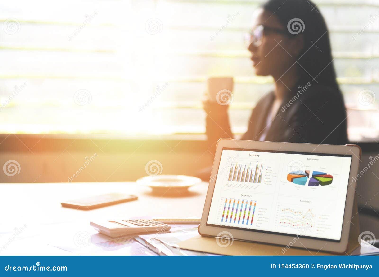 De bedrijfsgrafieken brengen op een tabletcomputertechnologie in kaart op de lijst en de vrouw die in bureau met koffiekop werken