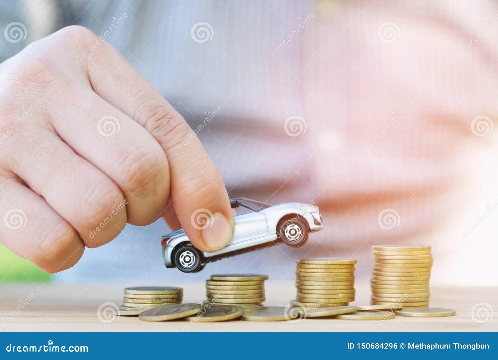 De bedrijfsmens en sluit omhoog het model van de handholding van stuk speelgoed auto op over een geld van gestapelde muntstukken