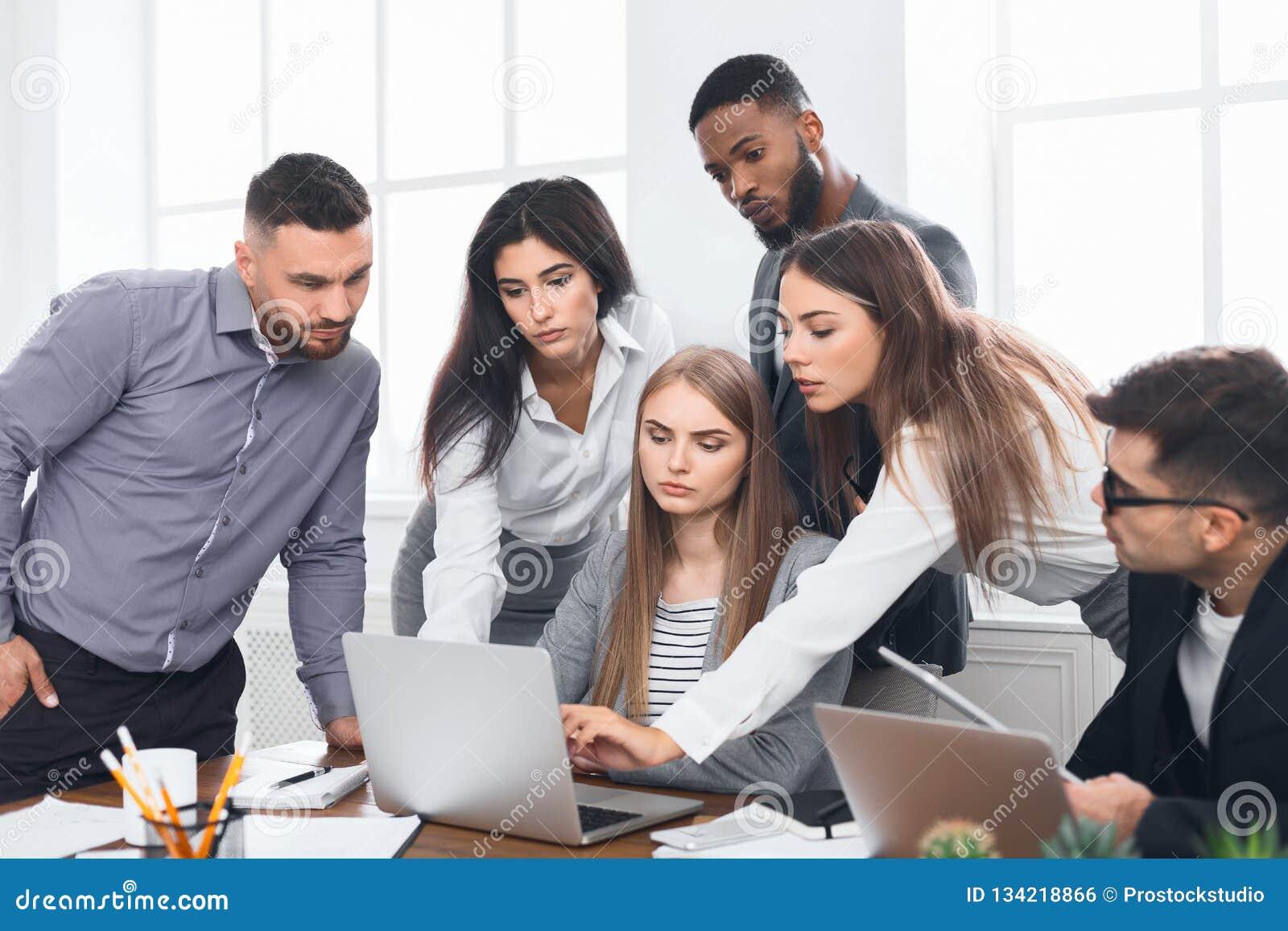 De bedrijfsmensen verzamelden zich rond laptop besprekend ideeën