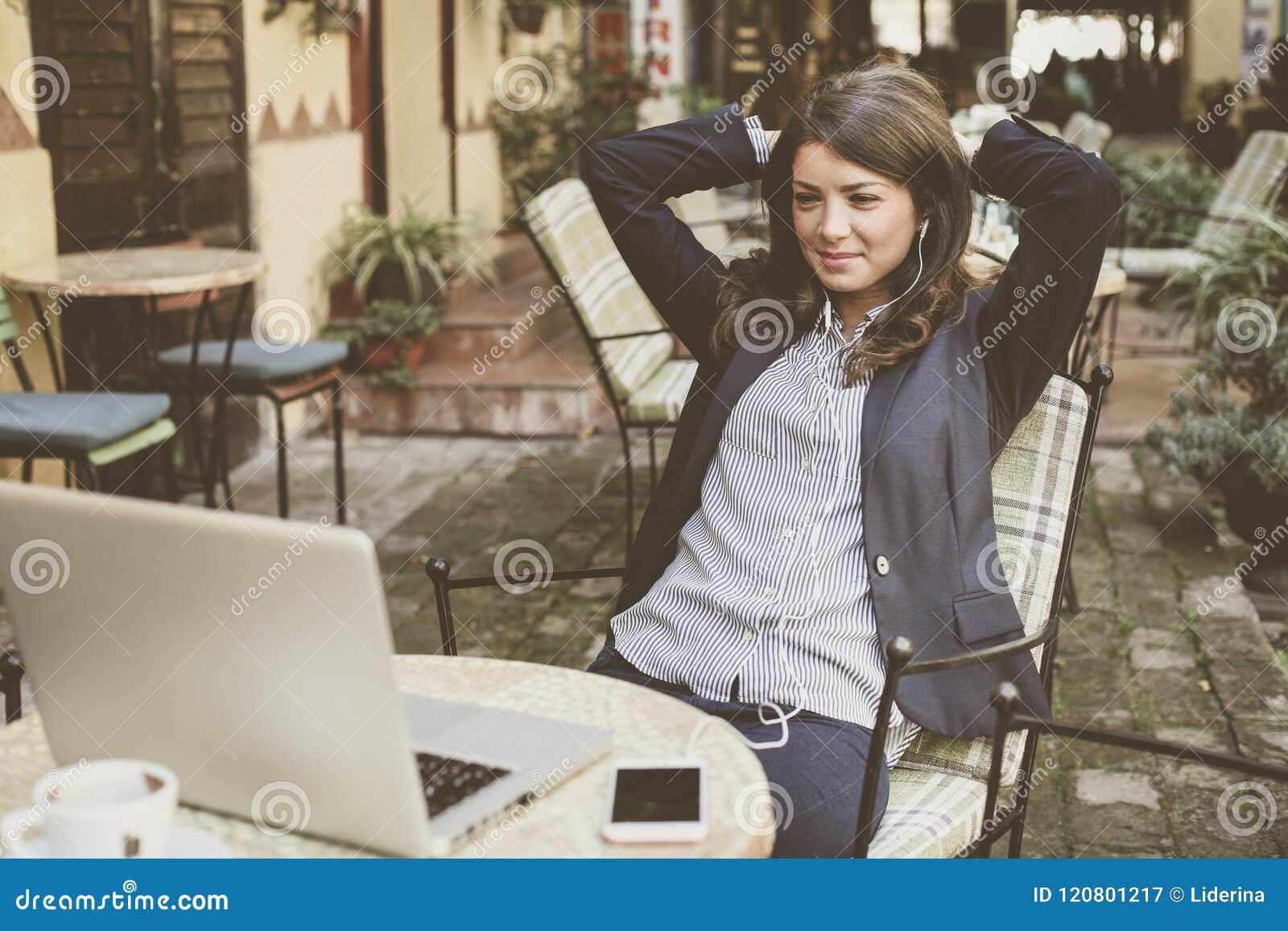 De bedrijfsvrouw bij koffie neemt een onderbreking van het werk Het luisteren muziek