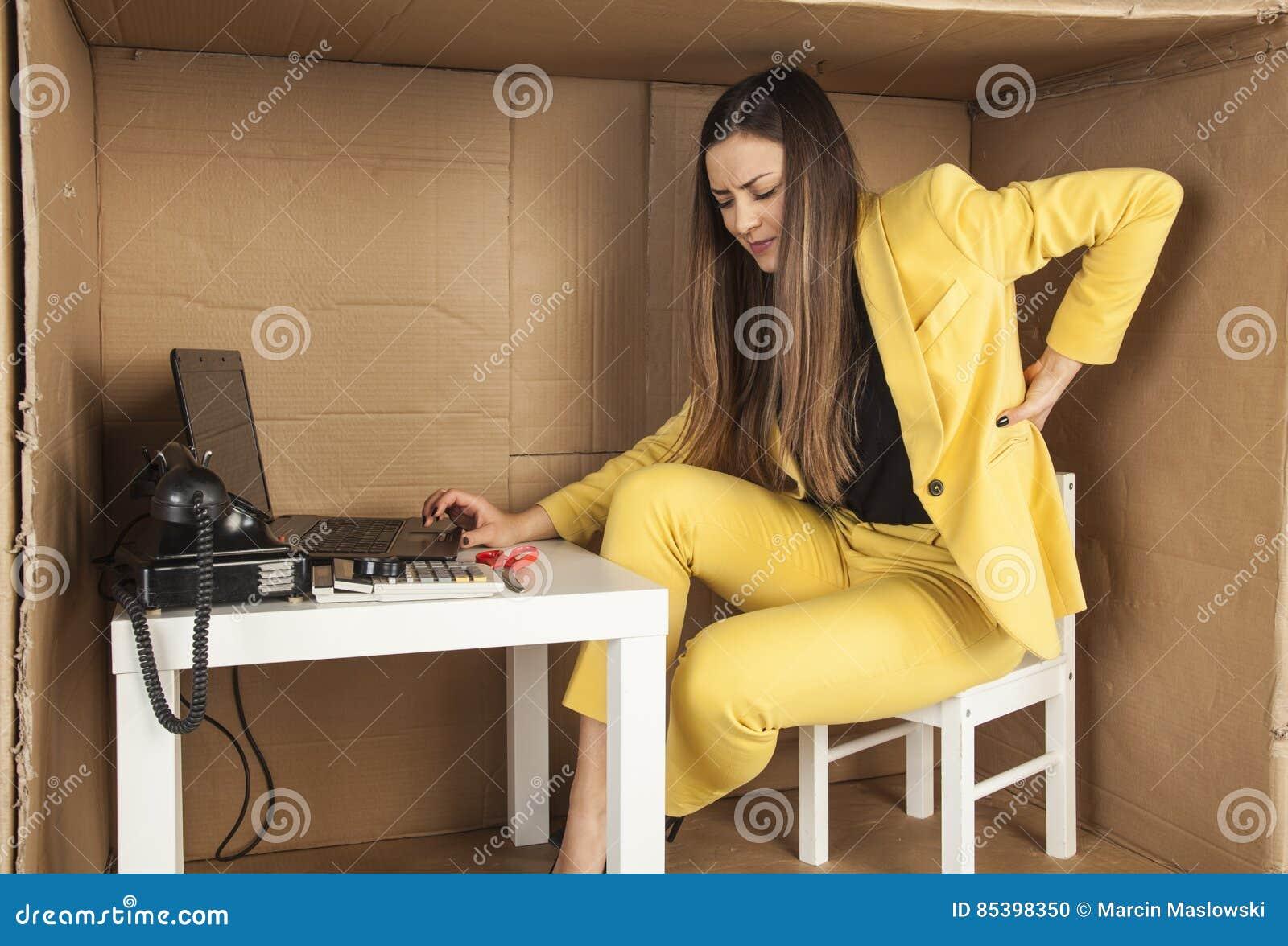 De bedrijfsvrouw heeft rugpijn van het werk in een klein bureau