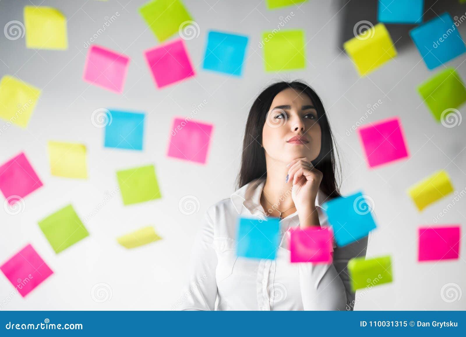 De bedrijfsvrouw lijmt stickers en het denken over het project Vrouw schaven die over stickers denken