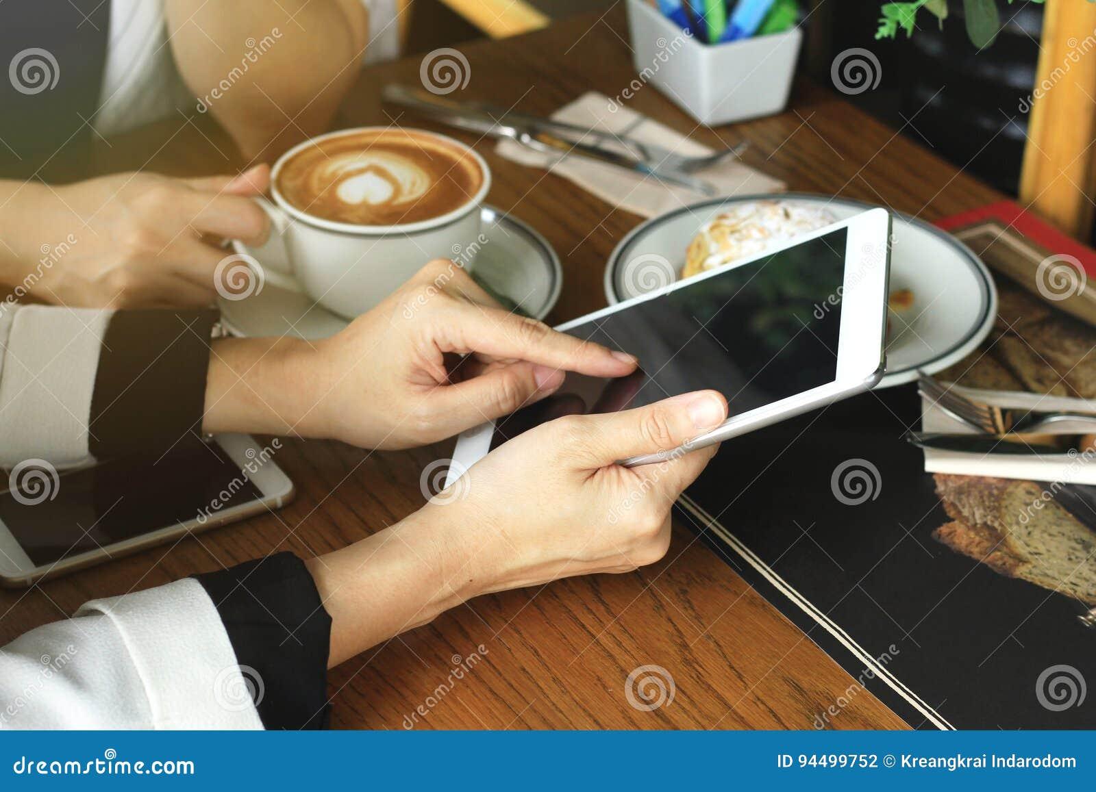 De bedrijfsvrouwen die de tabletcomputer bekijken, Collega s die zaken bespreken bij koffie, overal waar is een het werk plaatsco