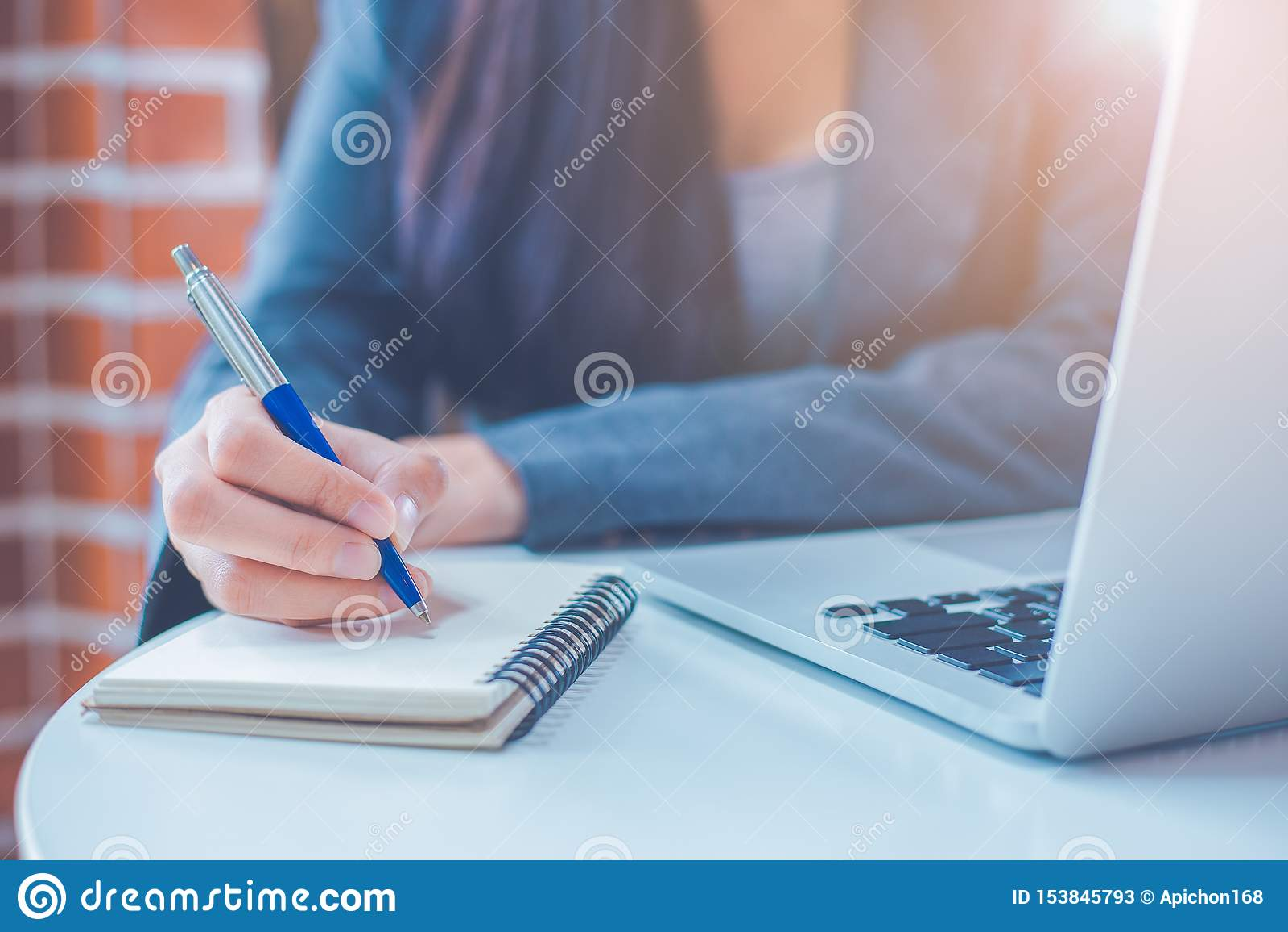 De bedrijfsvrouwenhand schrijft op een blocnote met een pen en heeft een laptop computer op het bureau in het bureau