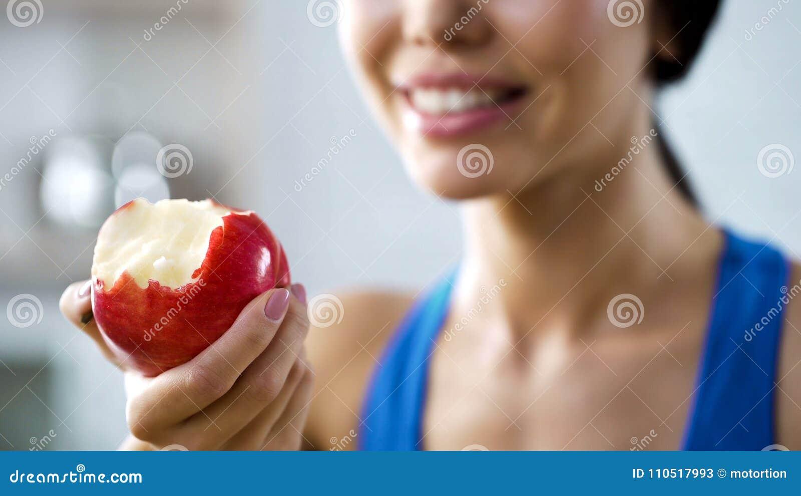 De beetappel die van de meisjesholding haar lichaam met vitaminen, gezonde tanden bijvullen