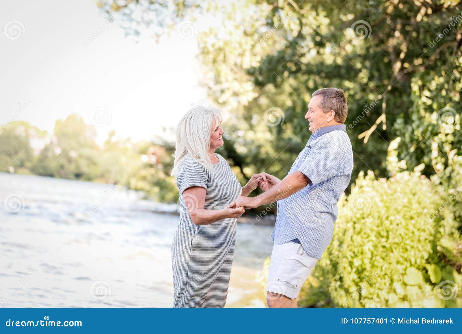 De bejaarde handen van de paarholding door het meer