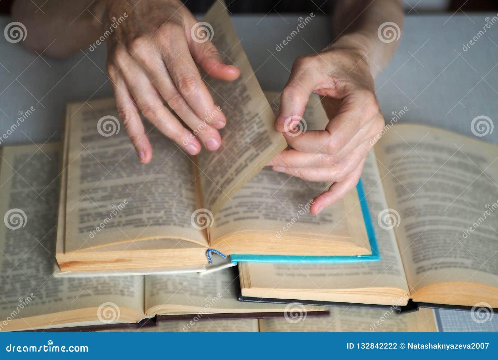 De bejaarde persoonshanden met geopende boeken, sluiten omhoog, geselecteerde nadruk, onduidelijk beeld