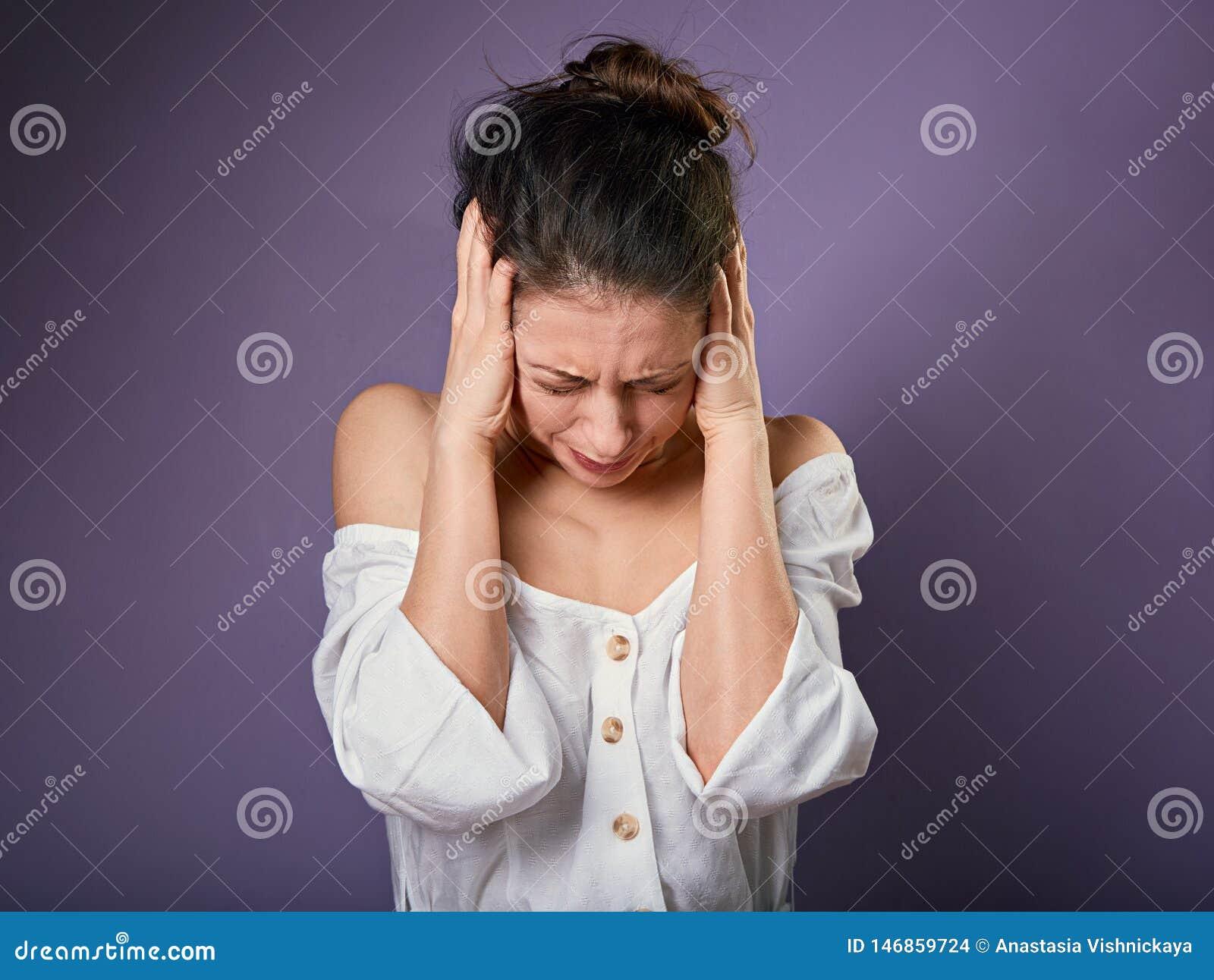 De beklemtoonde ongelukkige toevallige vrouw sloot oren de vingers omdat niet willen om het even welk geluiden en lawaai op purpe