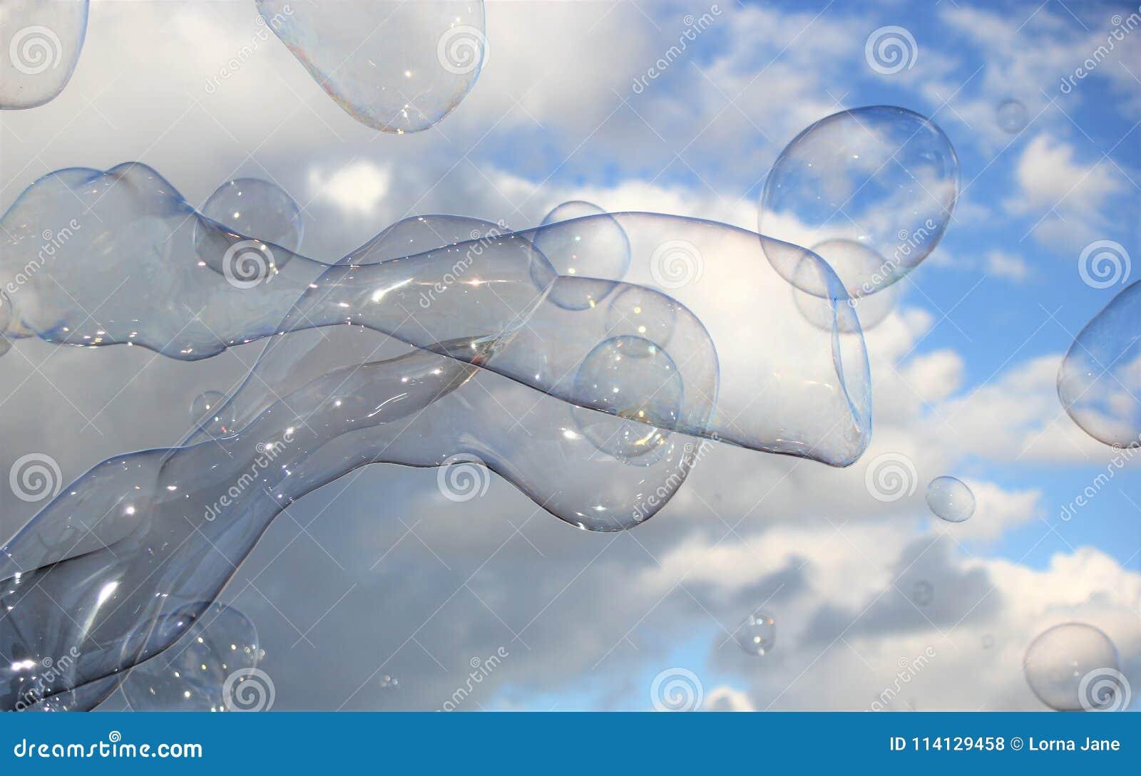 De bel borrelt drijvende zeepafwijking in blauwe hemel met wolken