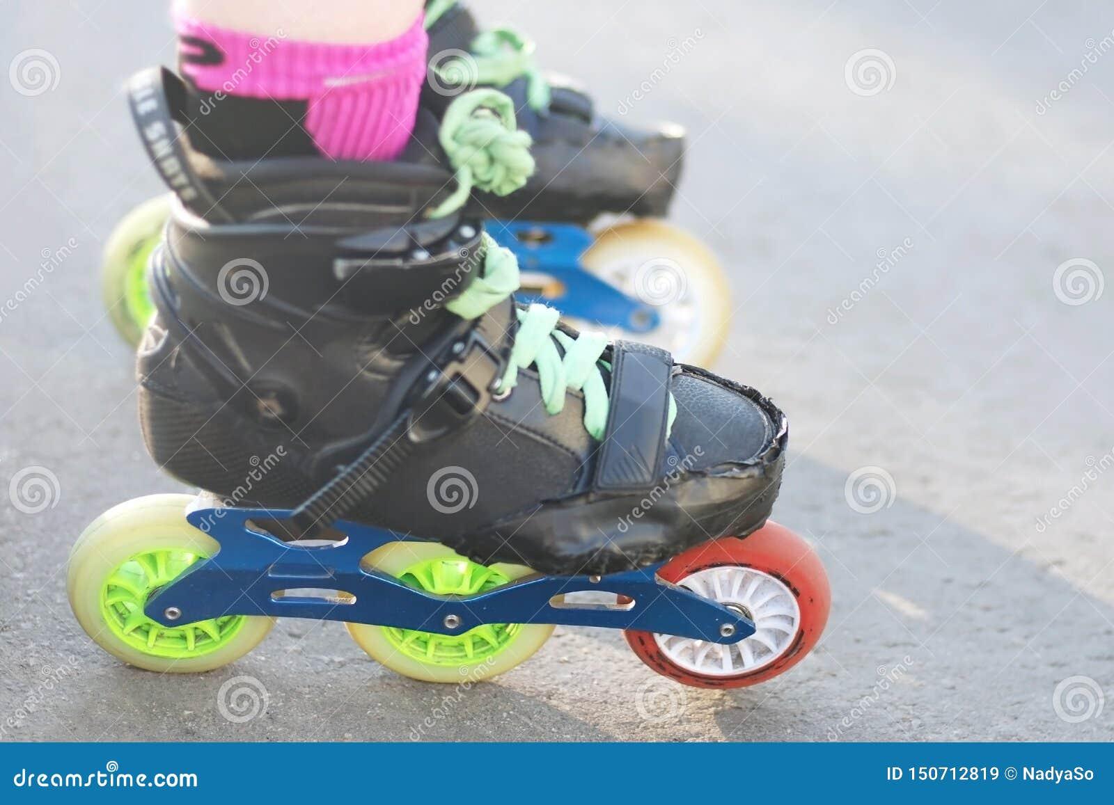 De benen die van de rol rollen voor het gealigneerde en slalom schaatsen dragen