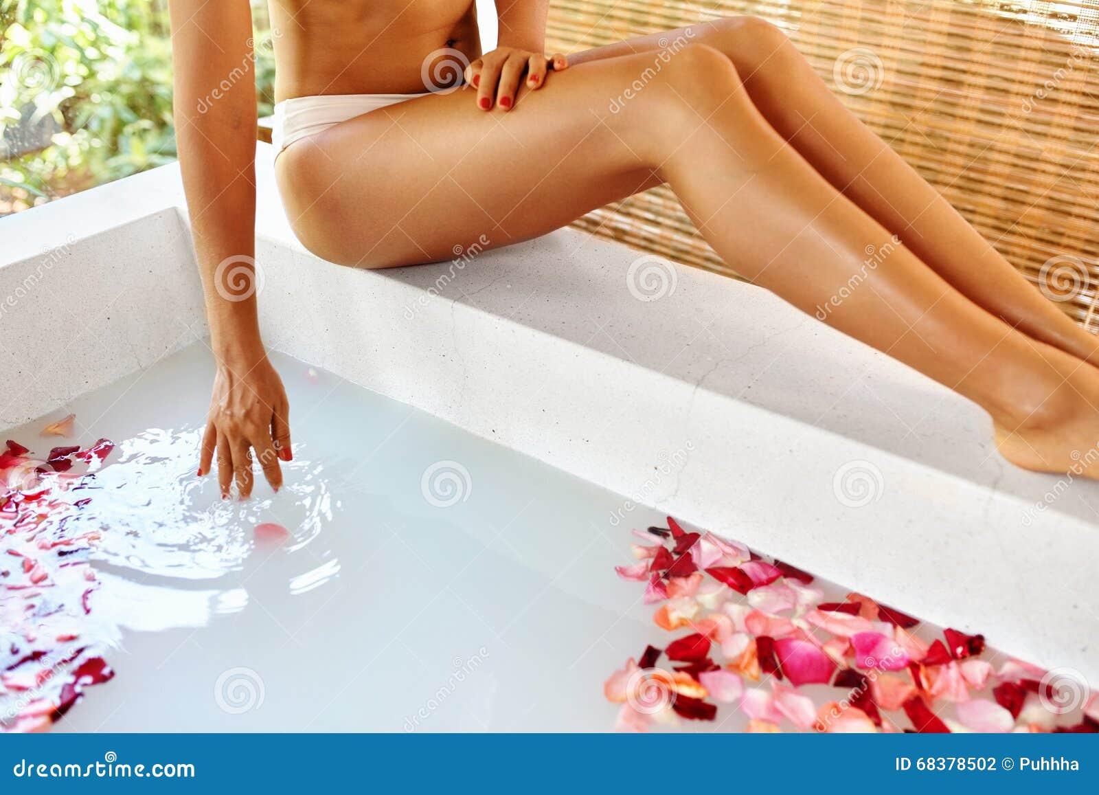 De benen van de vrouw De voet van de vrouw in het water Rose Flower Bath De Behandeling van de kuuroordhuid