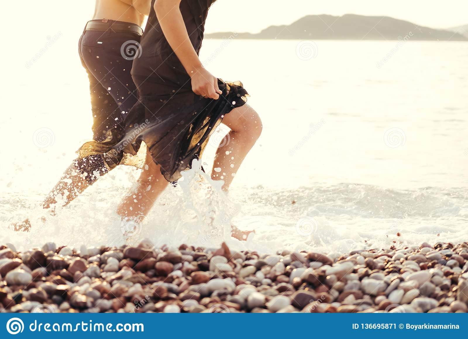 De benen van een man en een vrouw in een zwarte kleden het lopen over het overzees Bespattend water tegen de het plaatsen zon