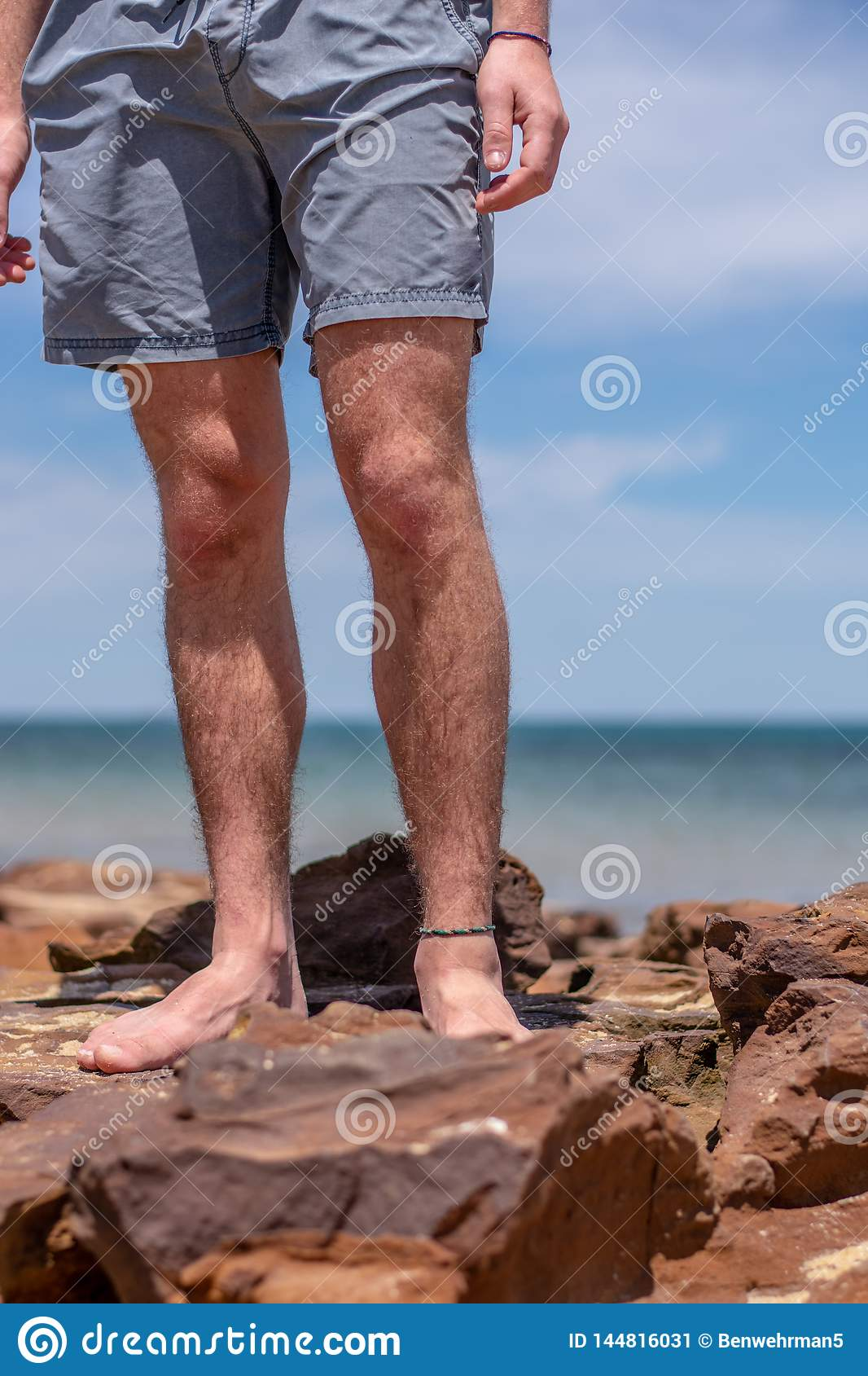 De Benen van de jongen op het Strand