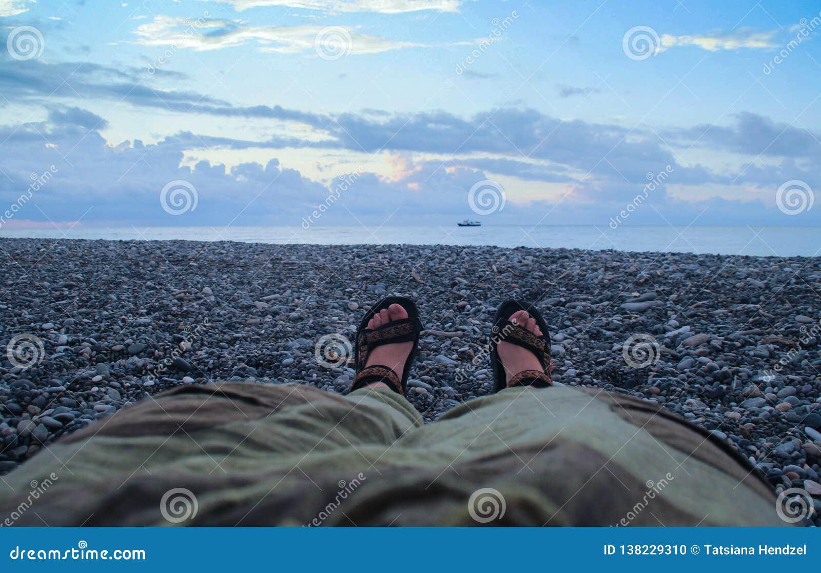 De benen van vrouwen in broek en sandals op naakte voeten op de zonsondergangstreek boven het overzees liggen op het strand