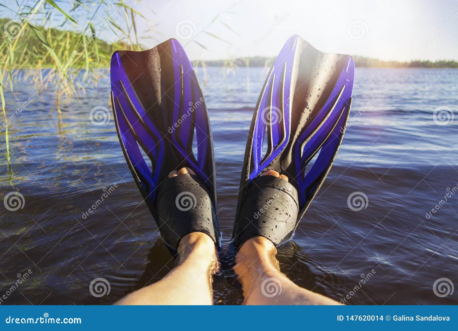 De benen van vrouwen in vinnen door het meer op een hete de zomerdag