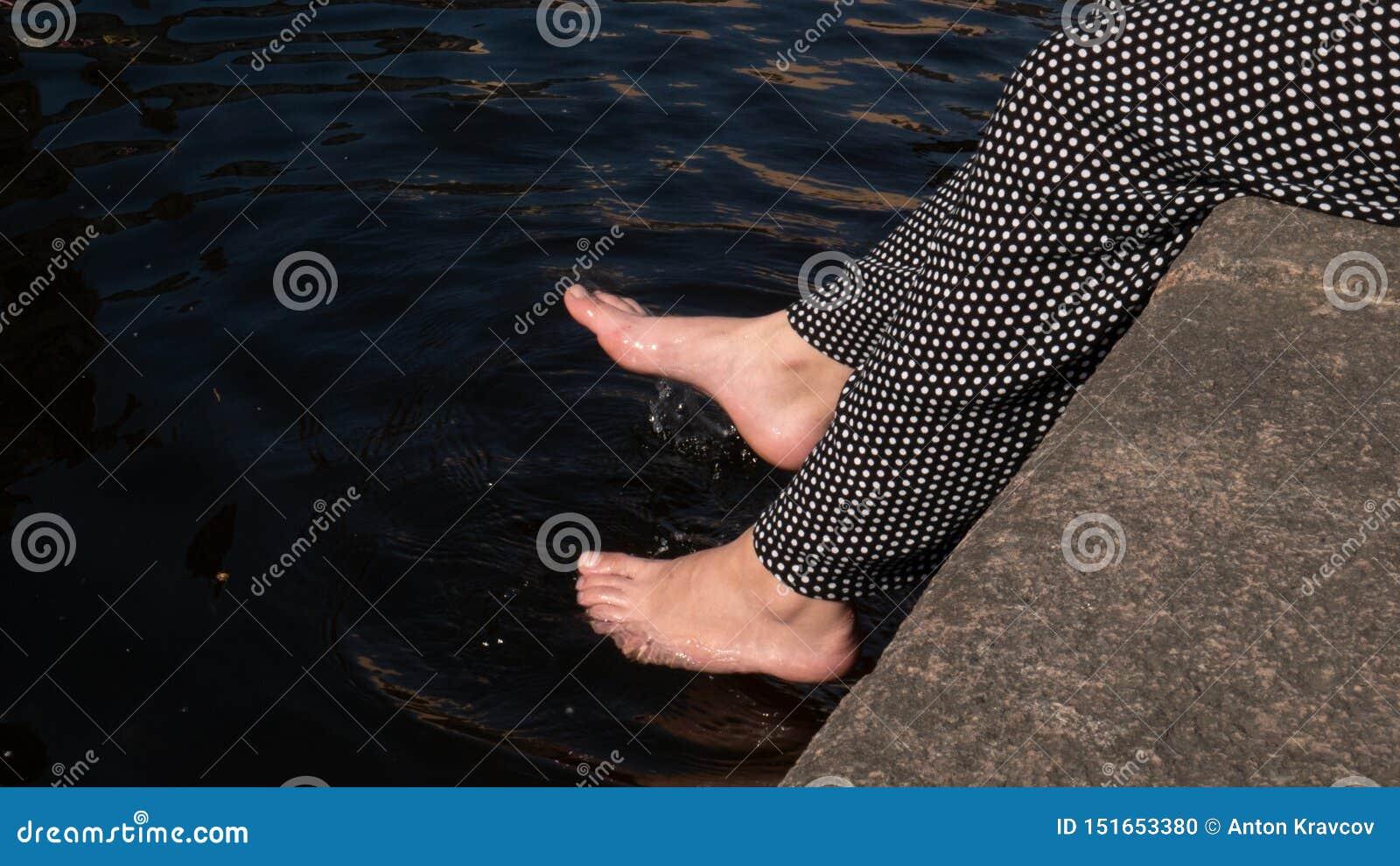 De benen van vrouwen werpen water Plons, de zomerstemming