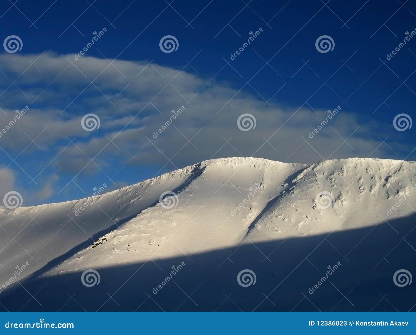 De berg en de wolken van de sneeuw