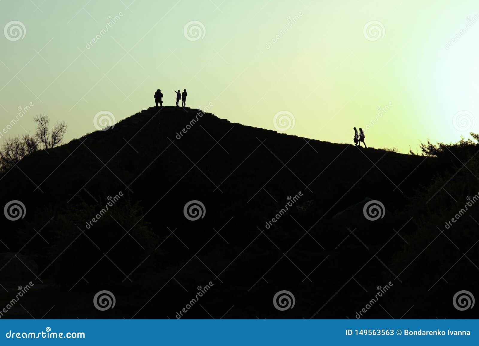 De bergbovenkant in schemer als zonsondergang, mensen bevindt die tegen de zon wordt zich gesilhouetteerd