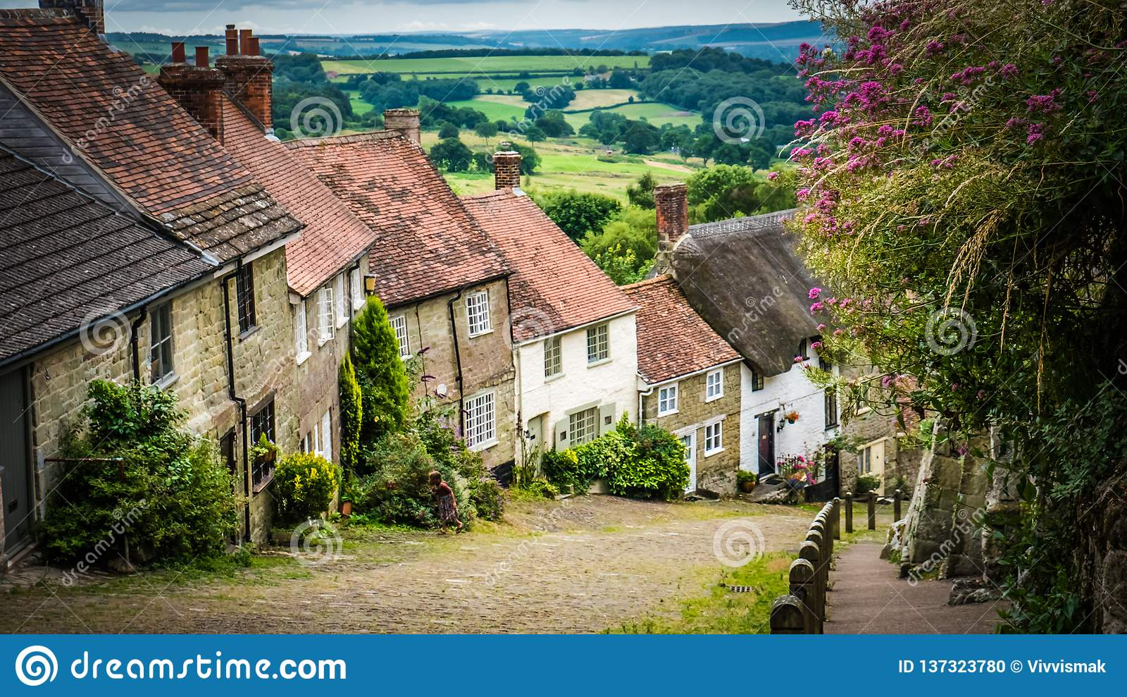 De beroemde Gouden Heuvel cobbled straat met oude met stro bedekte dakhuizen in Shaftesbury, het UK