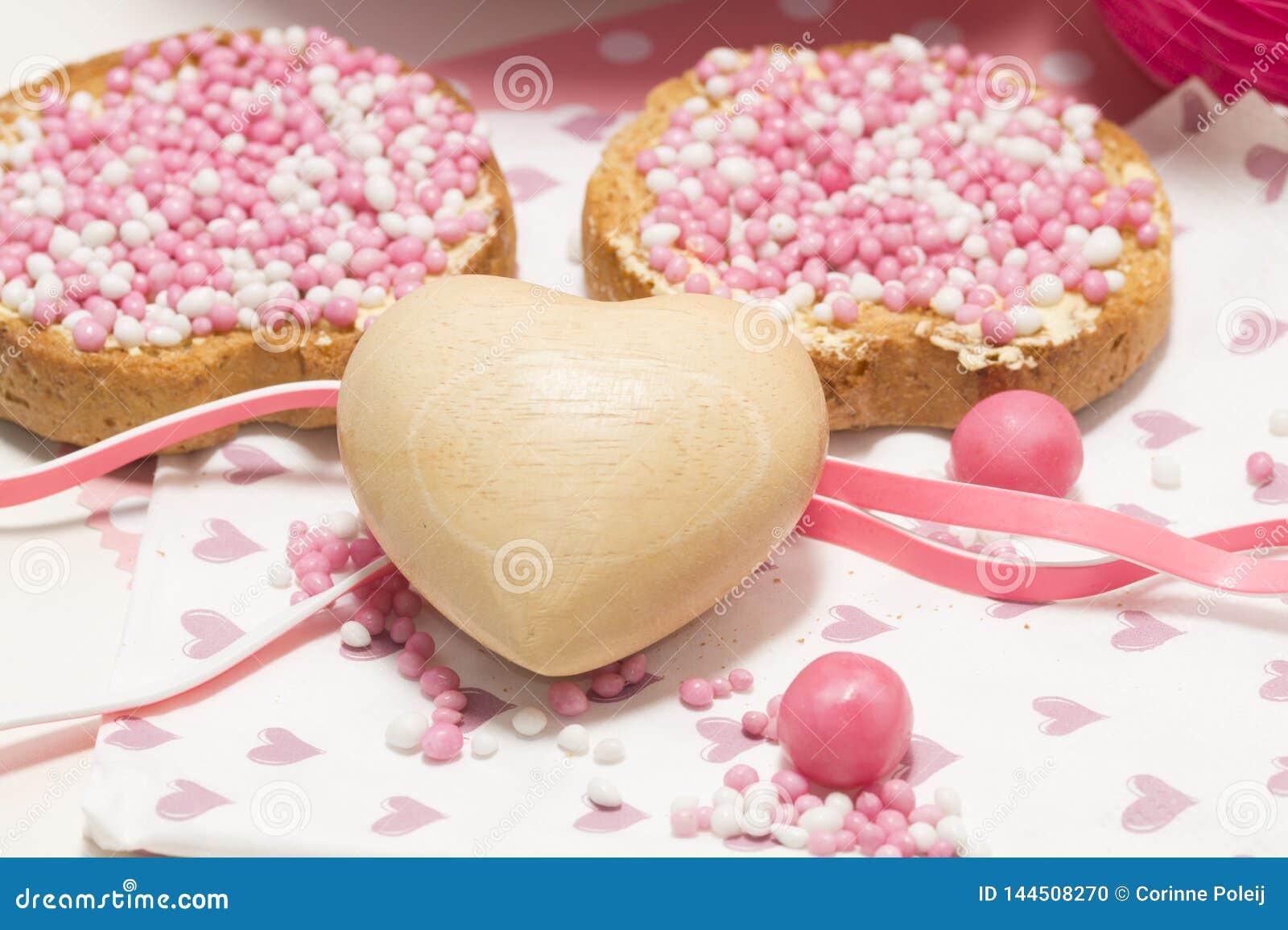De beschuit met roze anijszaadballen, muisjes, het typische Nederlands behandelt wanneer een babymeisje in Nederland geboren is
