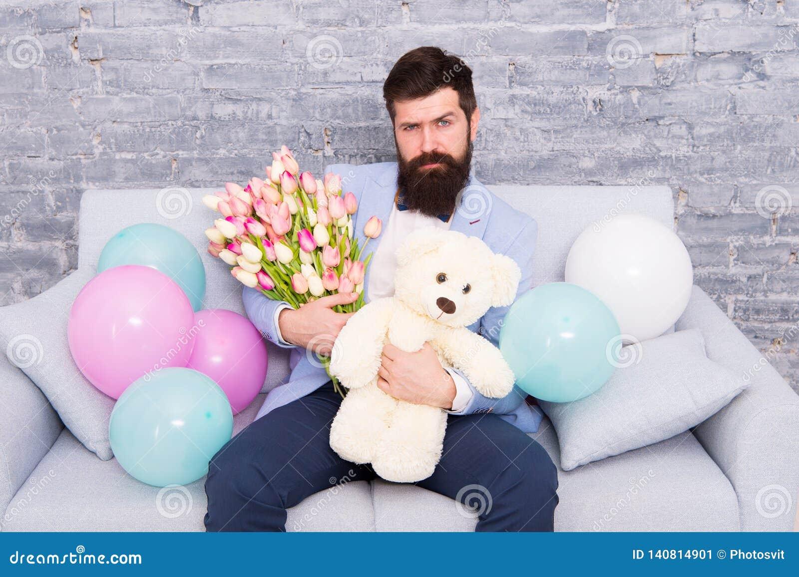 De beste manier te zeggen u geeft De lentegift Gebaarde mens hipster met de lentebloemen Bloem voor 8 Maart De datum van de liefd