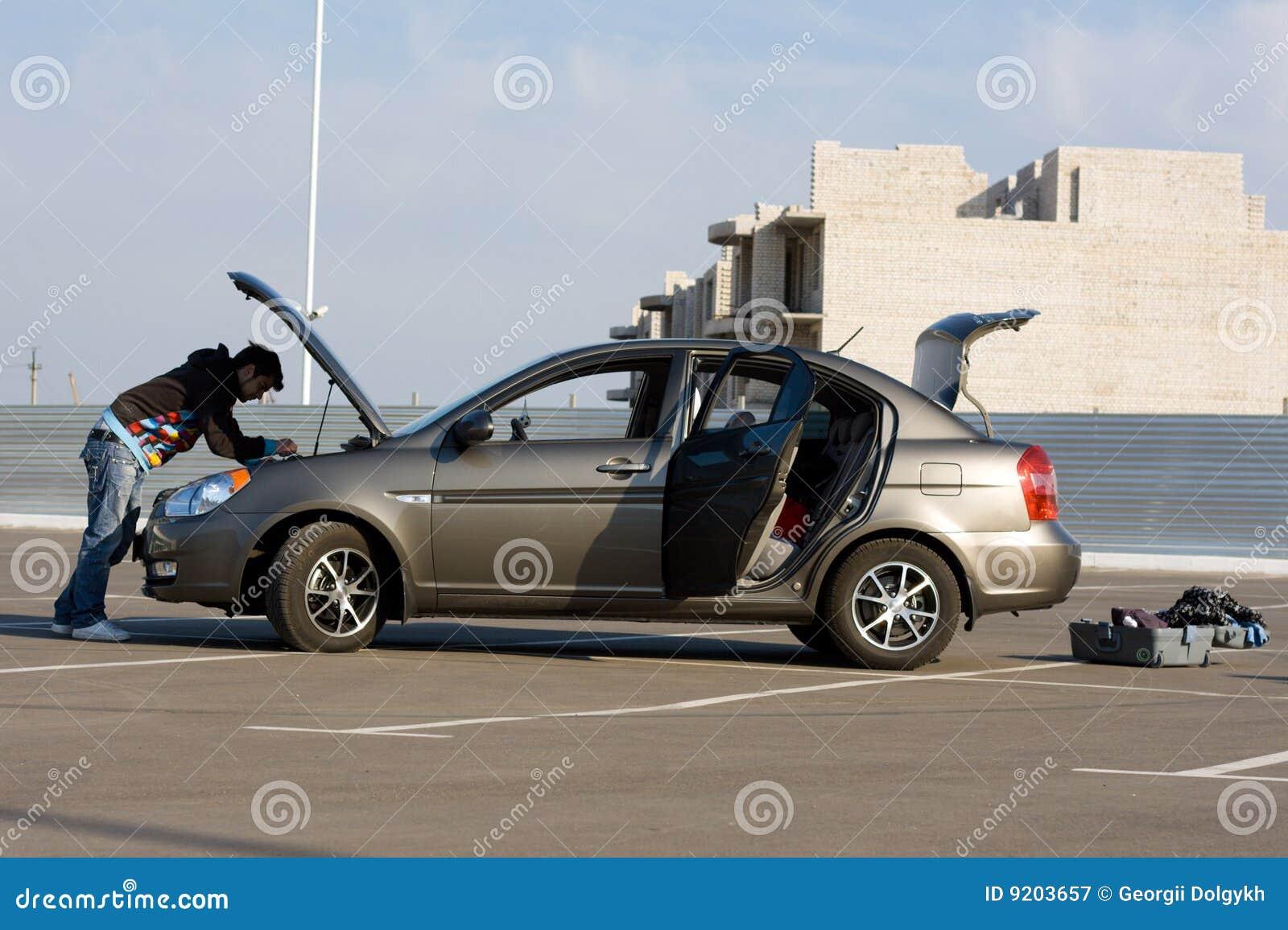De bestuurder die van de auto de motor van de auto onderzoekt