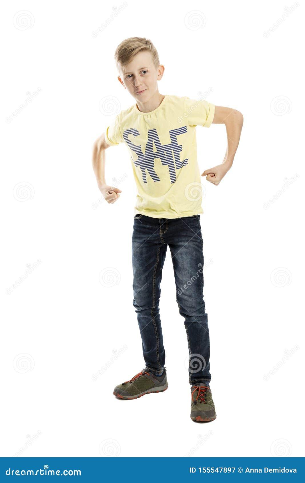 De bevindende tienerjongen in jeans en een gele T-shirt toont spieren volledige hoogte Ge?soleerd over witte achtergrond