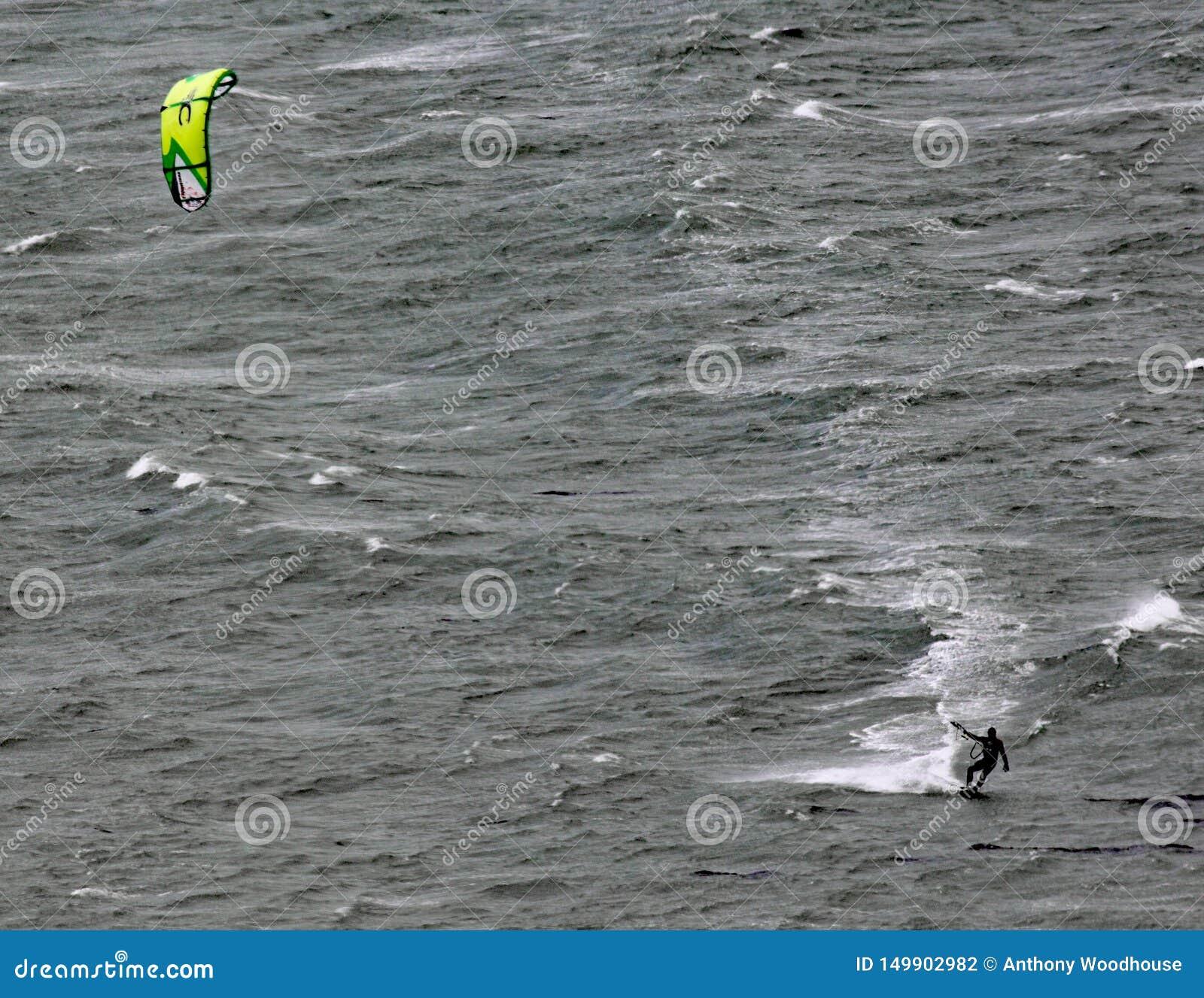 De bewegingen van een vliegersurfer over Lyall-Baai in Wellington New Zealand op een grijze stormachtige dag