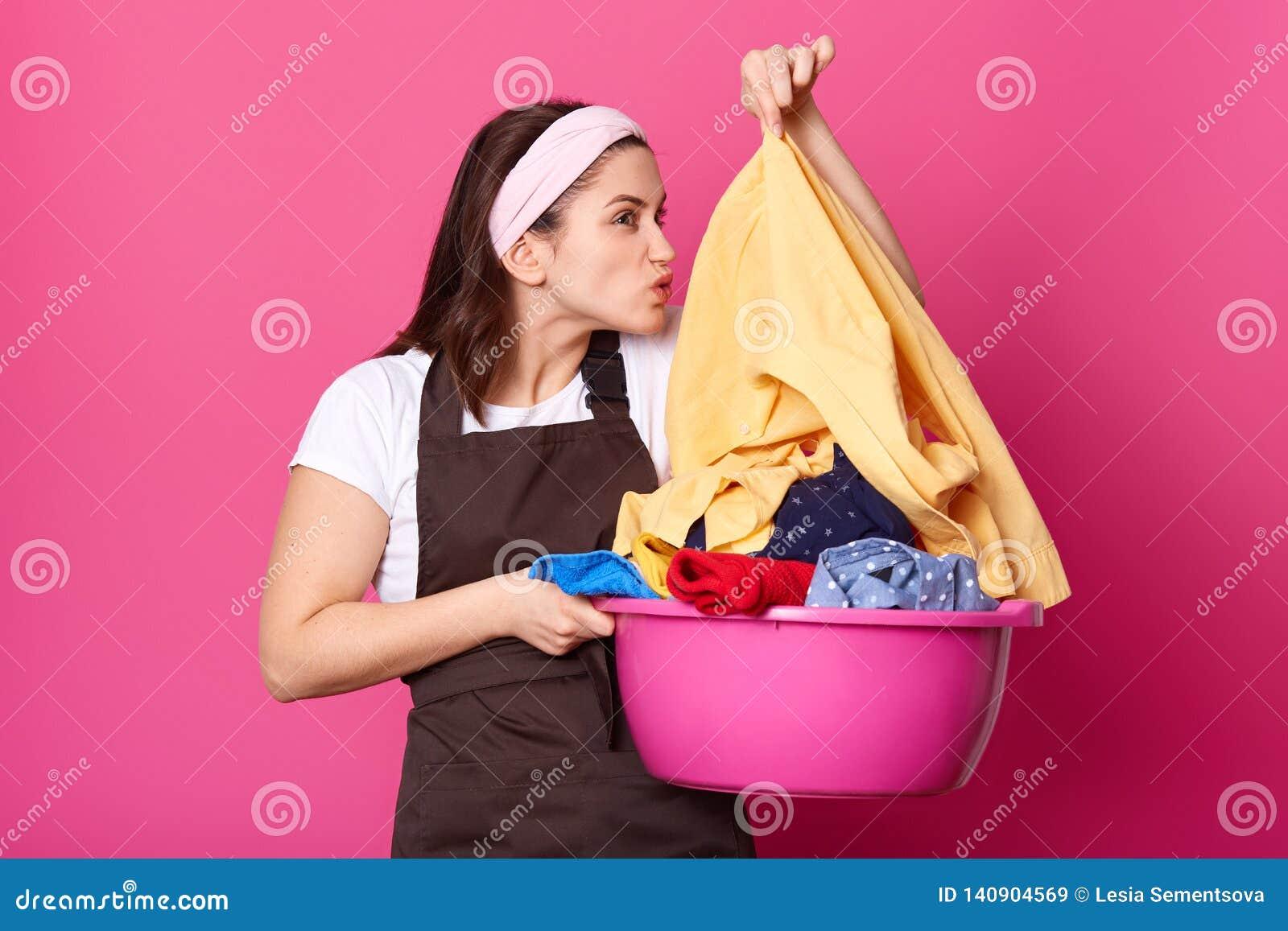 De bezige huisvrouw houdt bassin vuile kleren, doet was tijdens weekend, ruikt overhemd, gekleed in toevallige schort en hoofdban