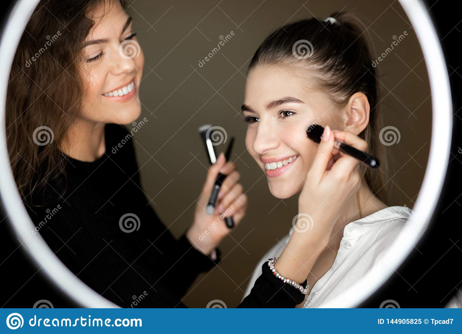 De bezinning in de spiegel van make-upkunstenaar het charmante meisje doet make-up aan een mooi jong meisje
