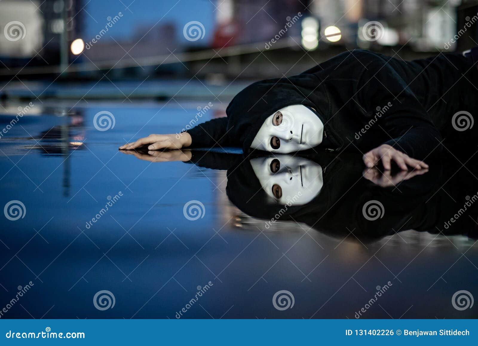 De bezinning van geheimzinnigheid hoodie de mens in wit maskergevoel drukte en stelde het liggen op natte vloer na de regen in te