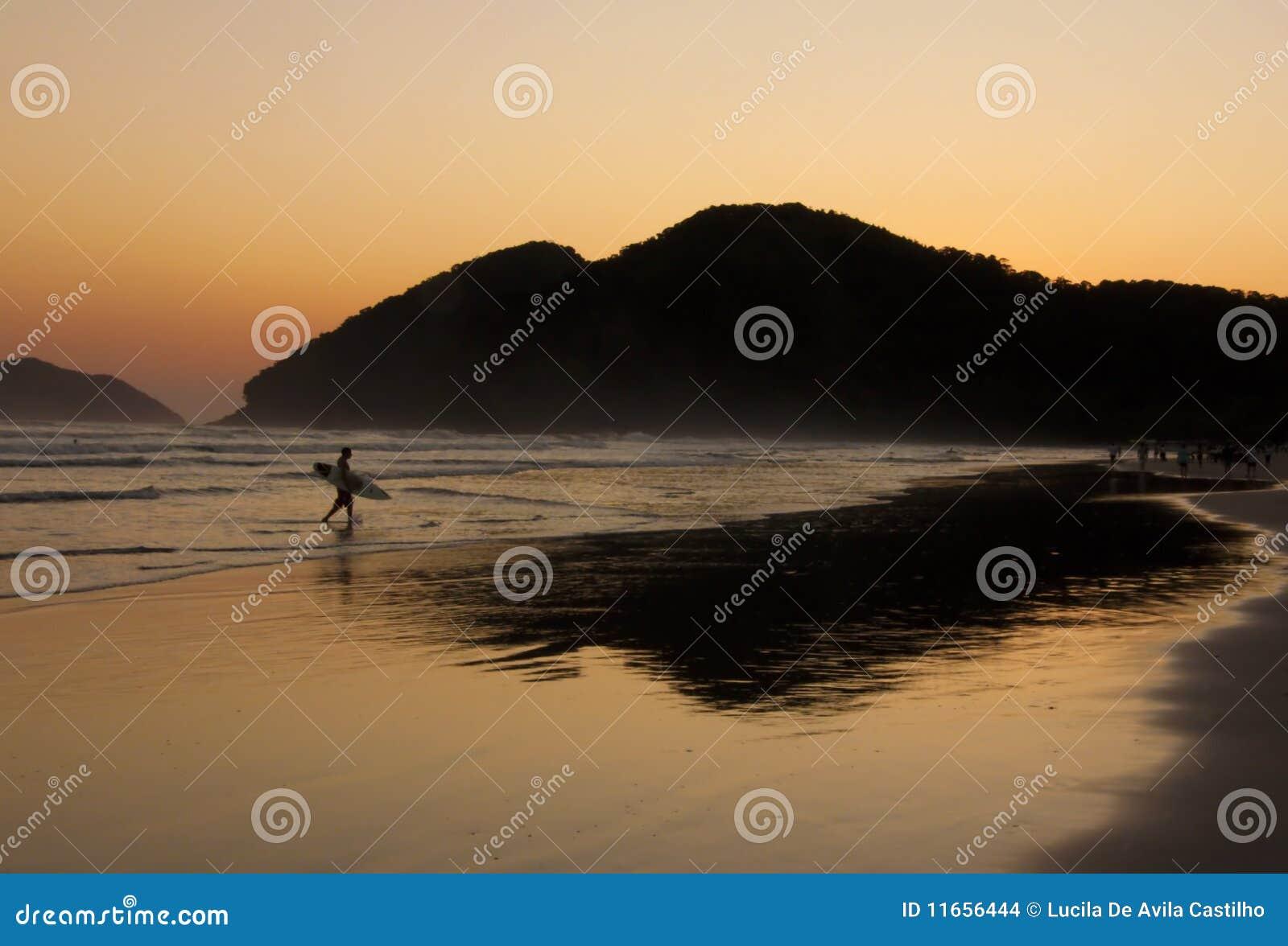 De Bezinning van Surfer en van de Zonsondergang bij een tropisch strand