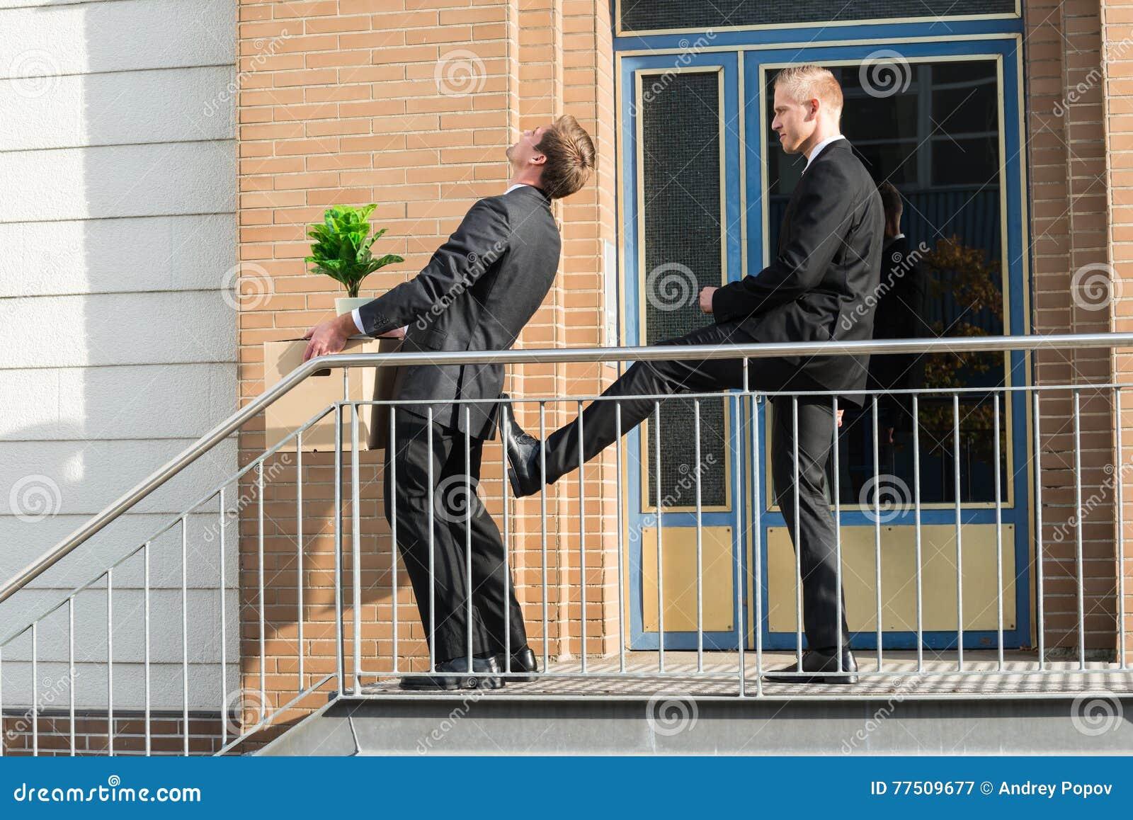 De Bezittingen van zakenmankicking employee with buiten Bureau