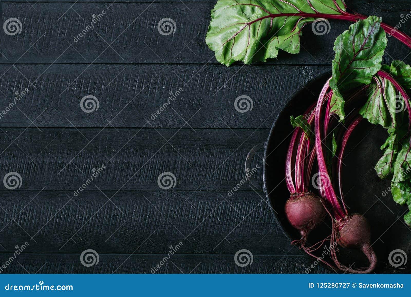 De bieten met groene bovenkanten in rond metaal filteren op donkere zwarte houten achtergrond, verse rode bieten op de mening van