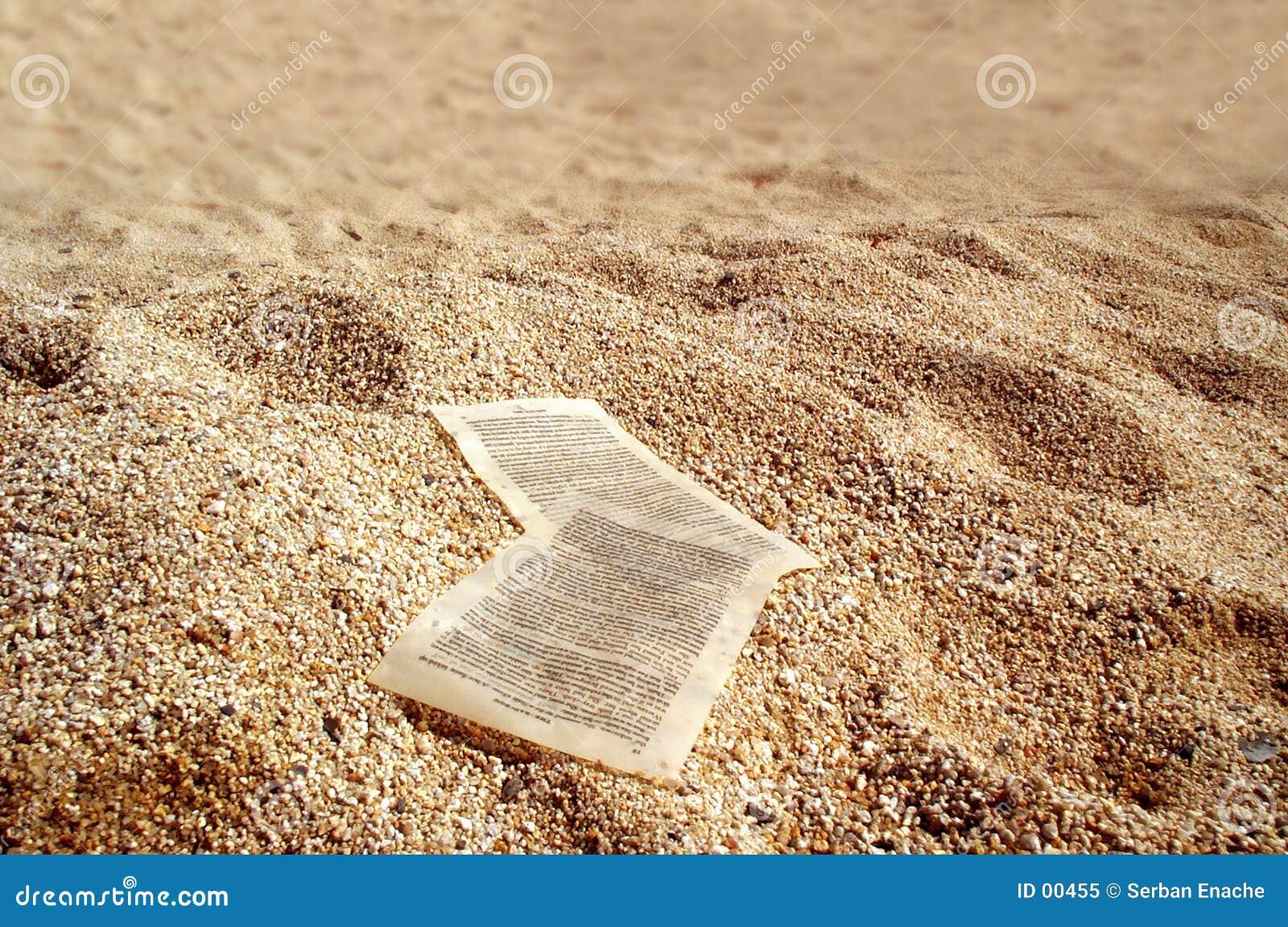 De bladen van het document op gouden zand