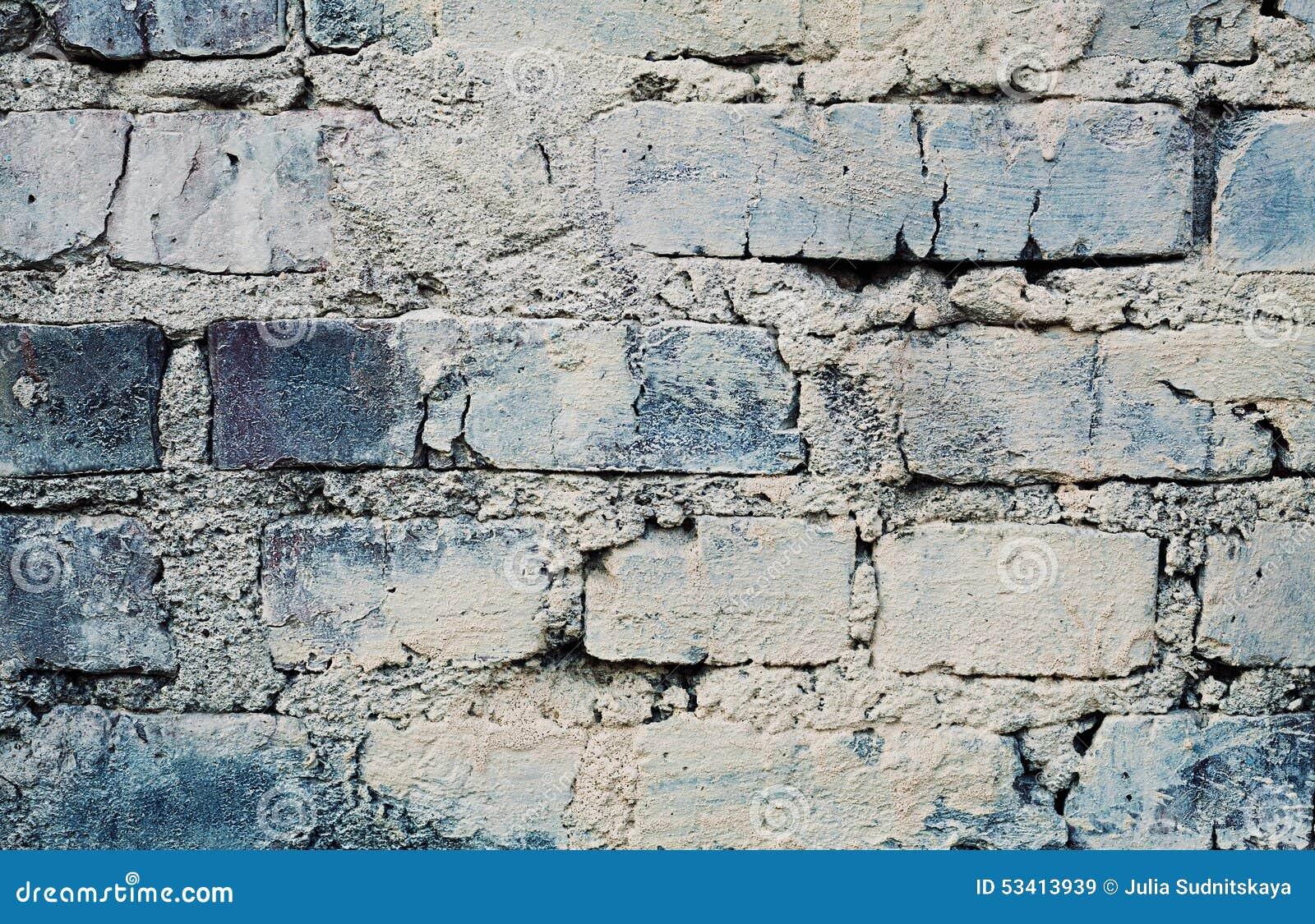 De blauwe bakstenen muur met barsten en schaaft, stedelijke zolderachtergrond