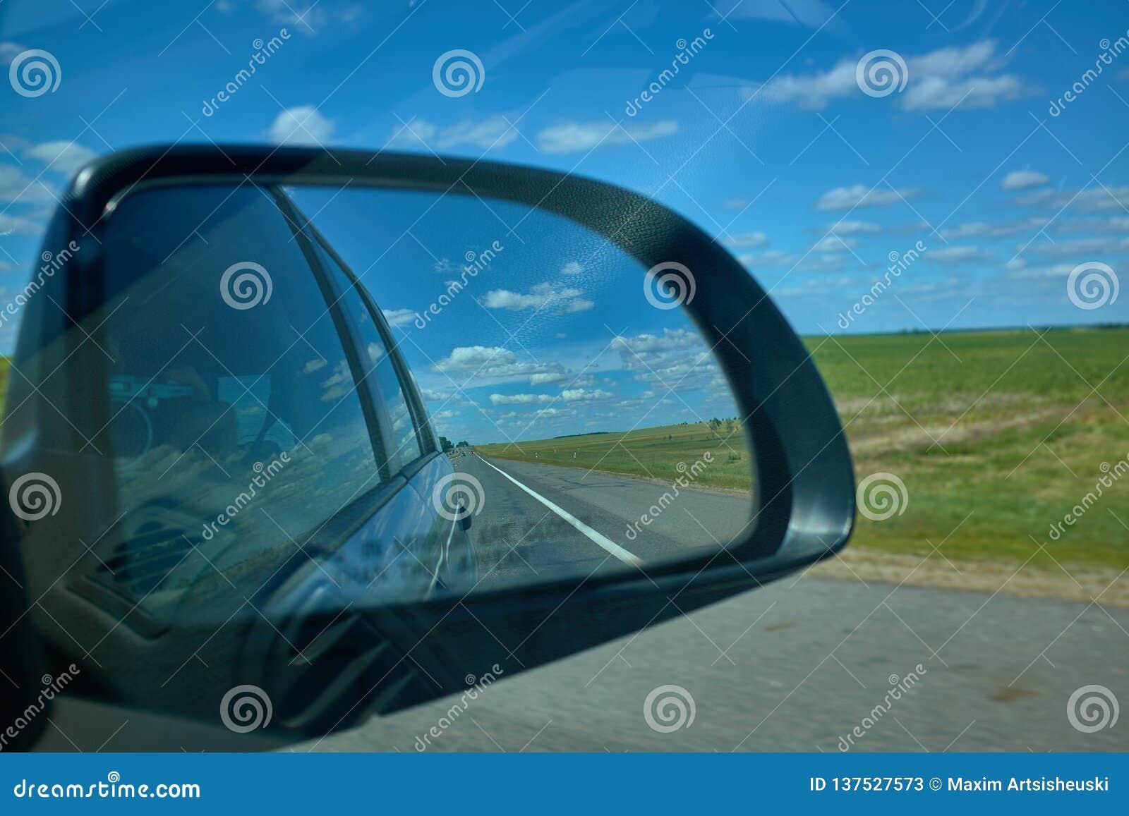 De blauwe bewolkte zonsondergang van het hemellandschap denkt in spiegel van auto na