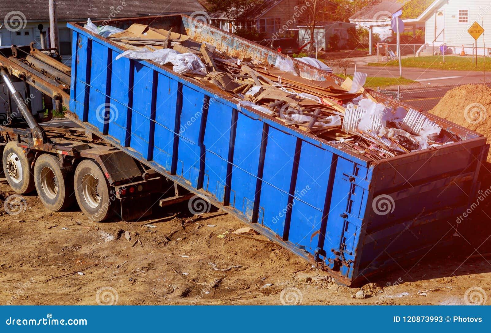 De blauwe die container van het bouwpuin met rots en concreet puin wordt gevuld Industriële huisvuilbak