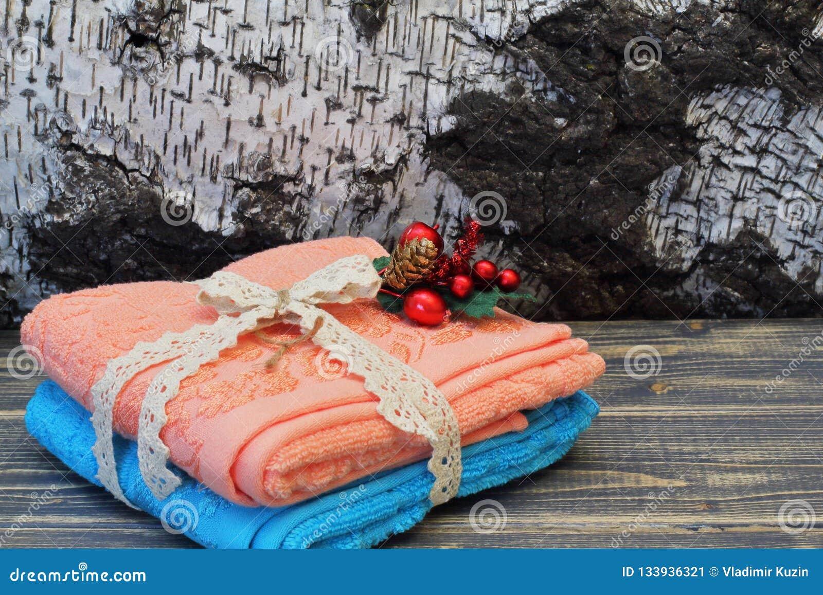 De blauwe en roze katoenen handdoeken bonden met een openwork vlecht en een decoratief mooi boeket tegen de achtergrond van berke