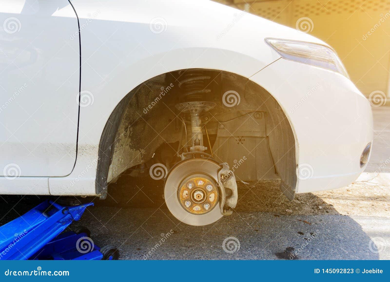 De blauwe hydraulische auto s van de de hefbomenlift van de autovloer om lekke banden op de weg te veranderen Dichtbij geplaatste