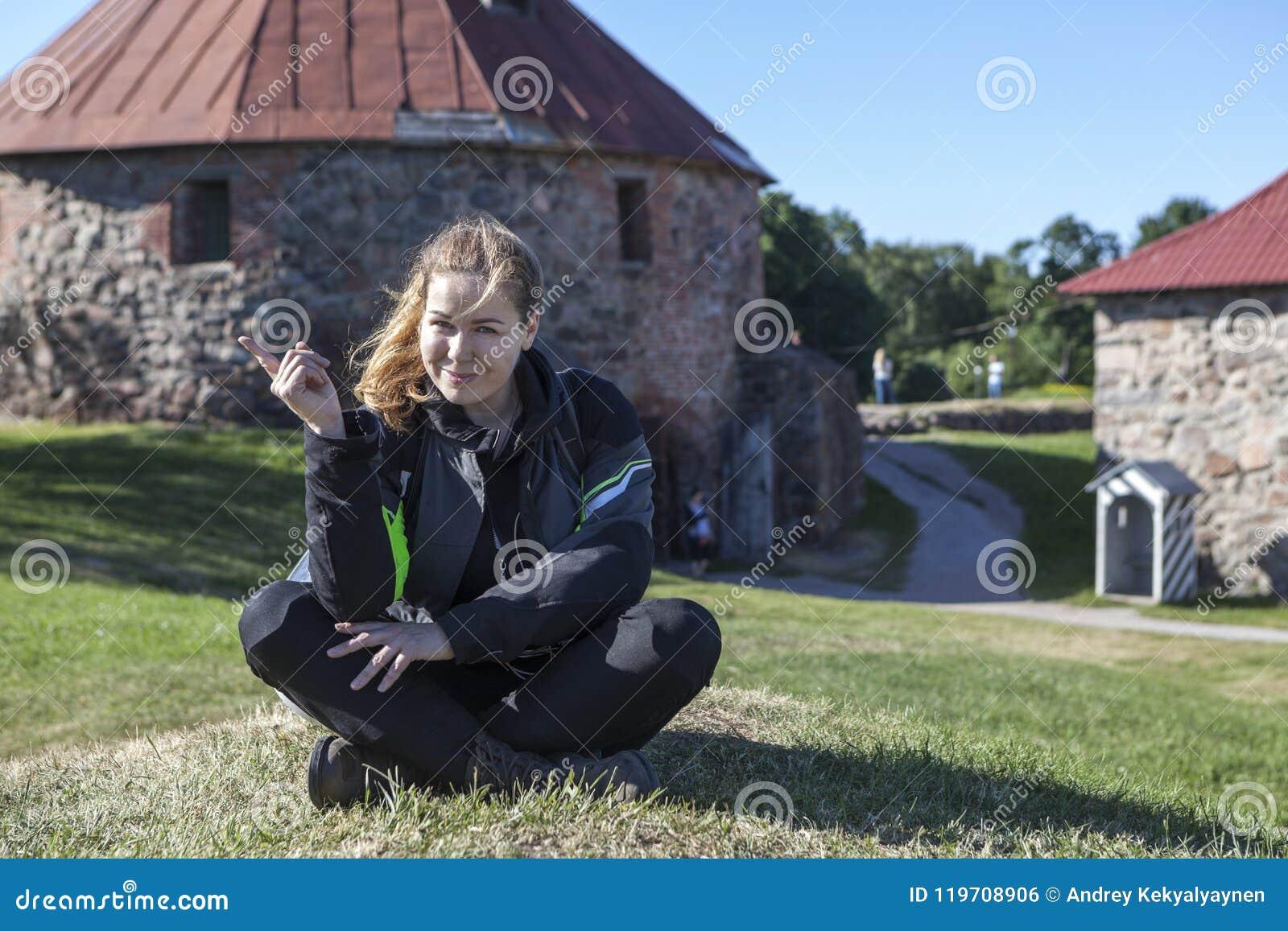 De blije Kaukasische vrouw in motorfietsjasje, knie bewaakt het zitten op groene weide in één of ander oriëntatiepunt, copyspace