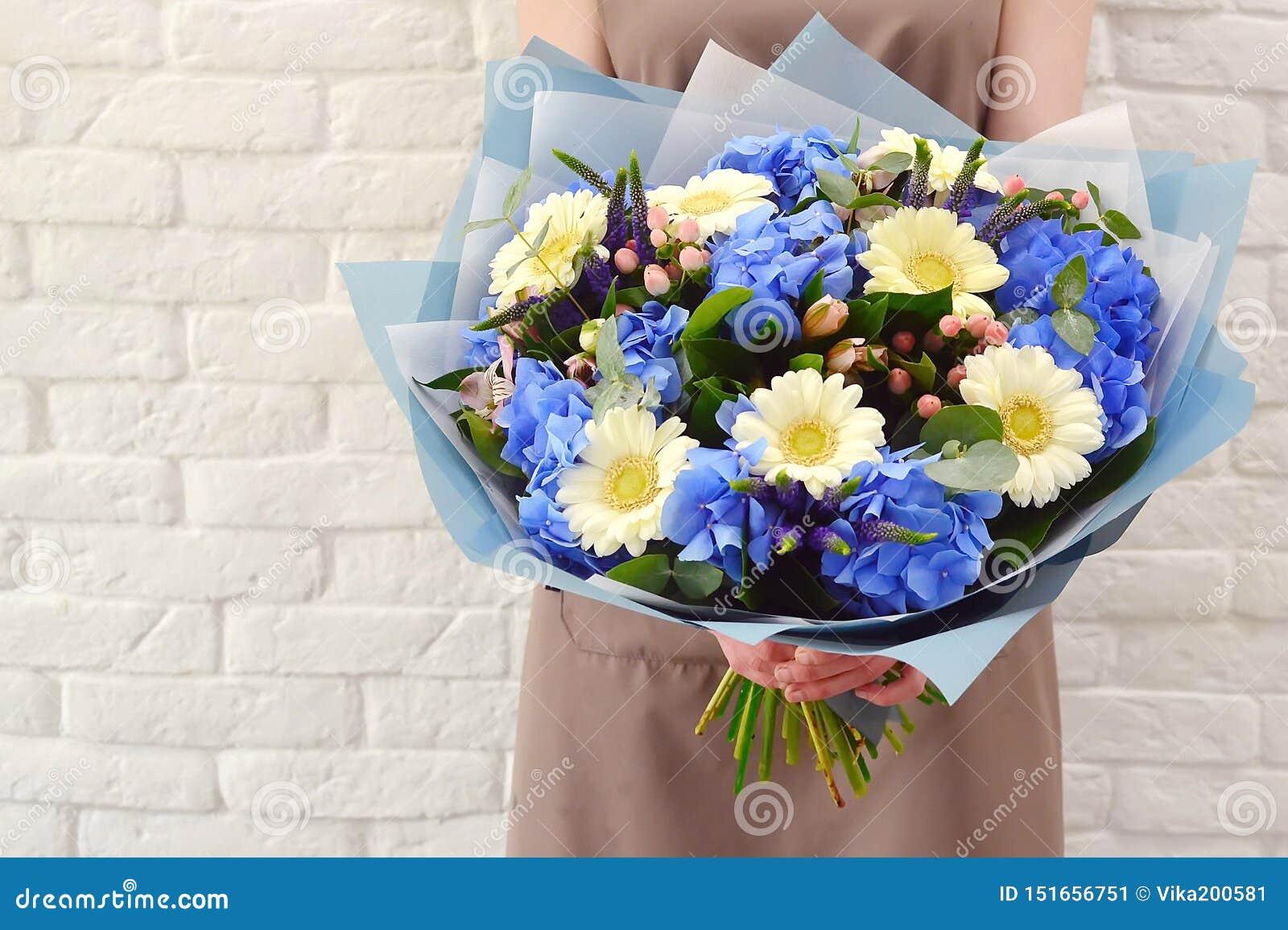De bloemist met een mooi boeket van bloemenhanden