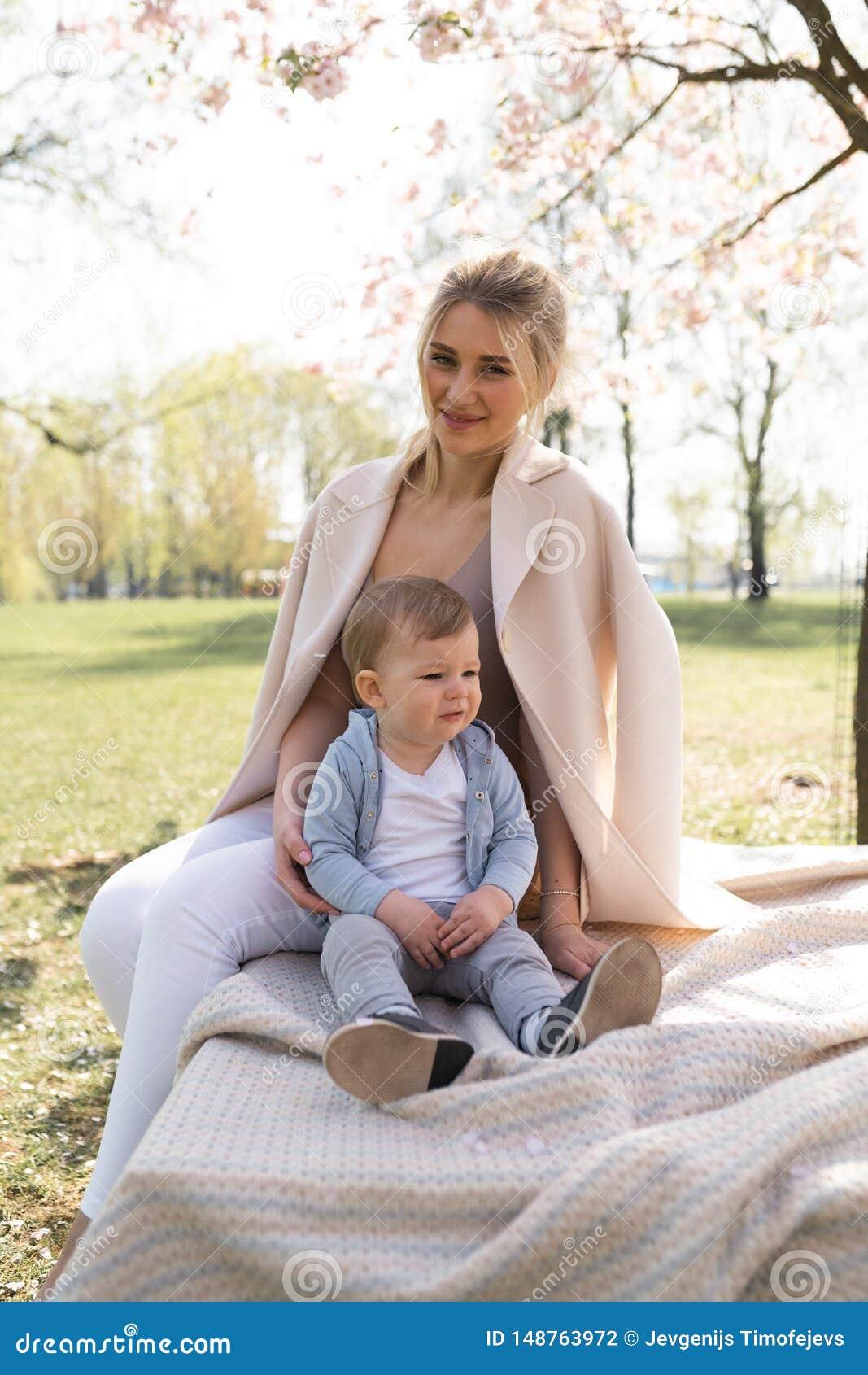 De bloesem van de Sakurakers - de jonge zitting van de mammamoeder met haar weinig zoon van de jongensbaby in een park in Riga, L