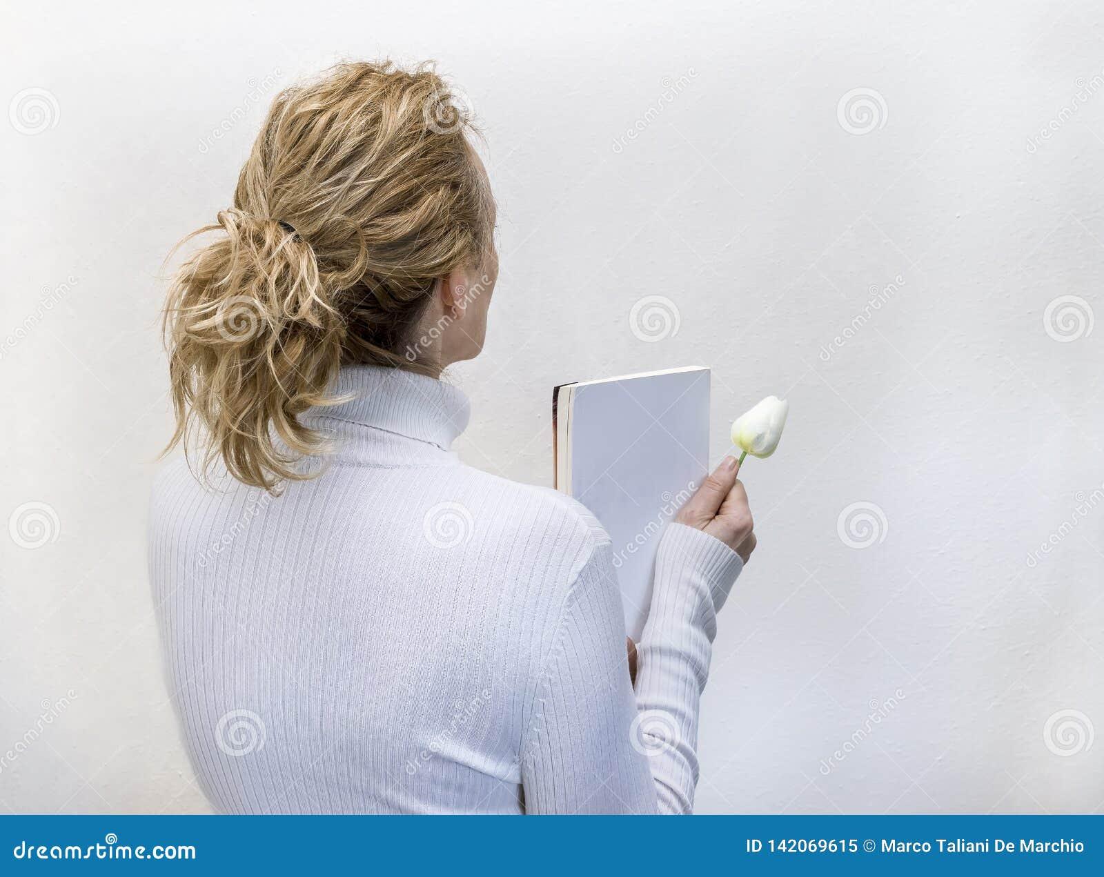 De blonde vrouw kleedde zich in wit die een boek en een witte bloem houden tegen een volledig witte achtergrond