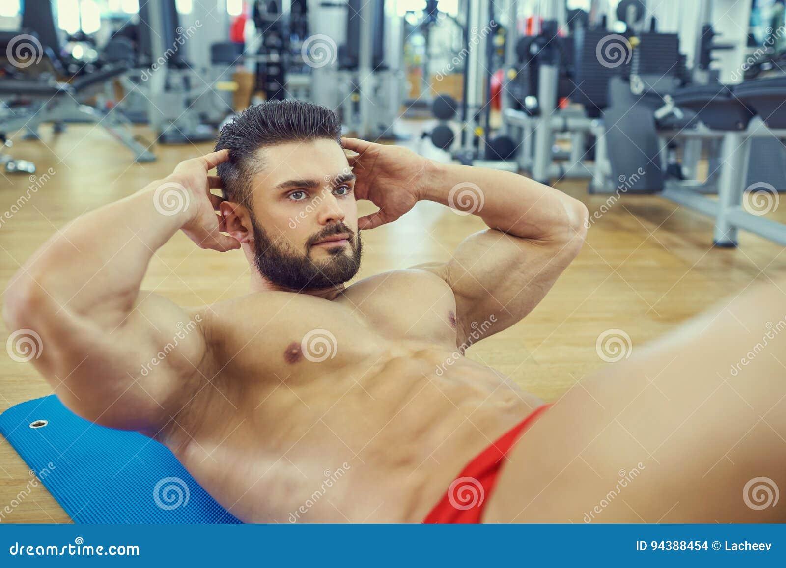 De bodybuilder met een baard doet abs oefening op de vloer in g