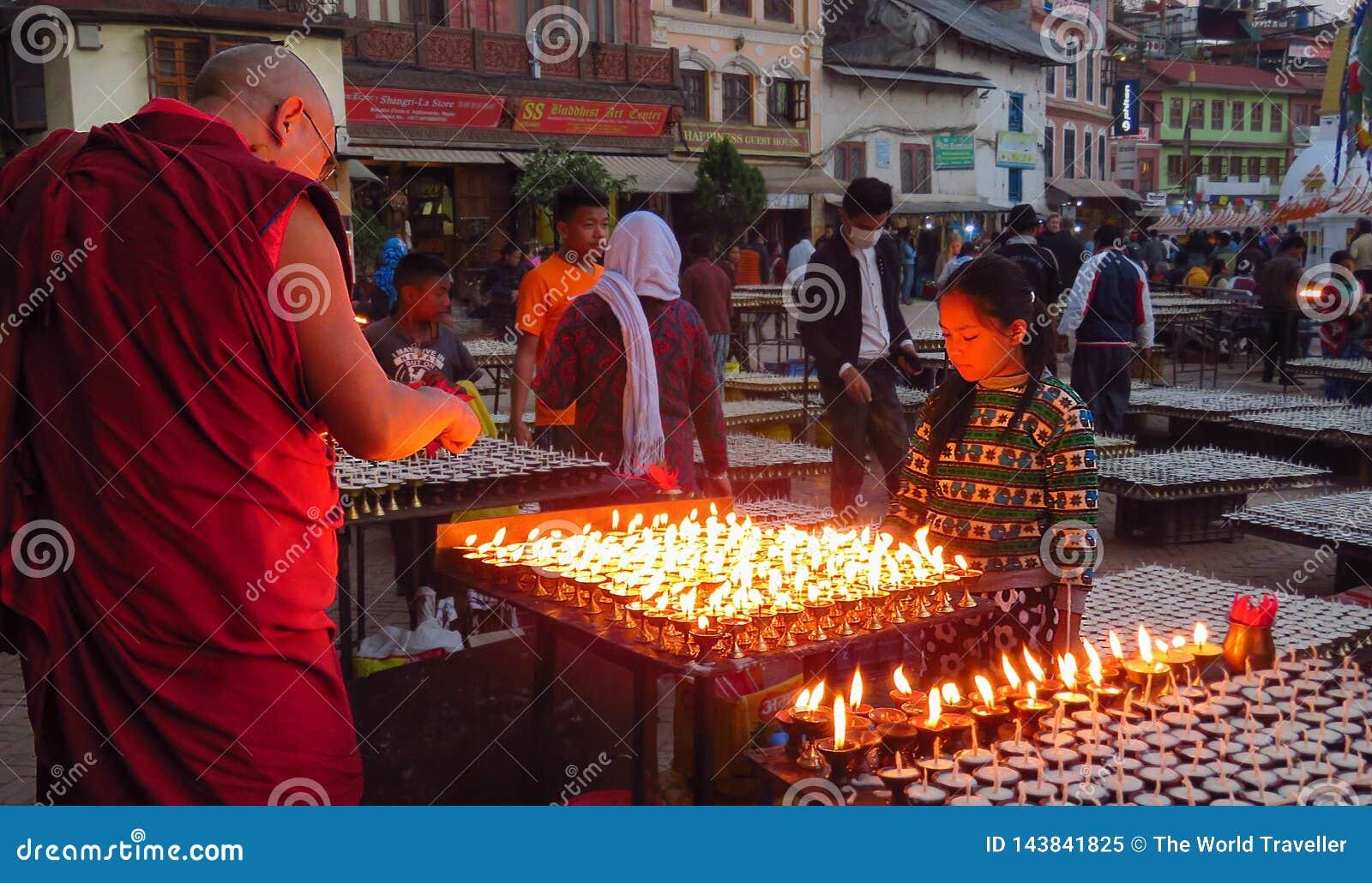 De boeddhistische monnik steekt een het bidden kaars, Boudhanath-stupa, Katmandu, Nepal aan