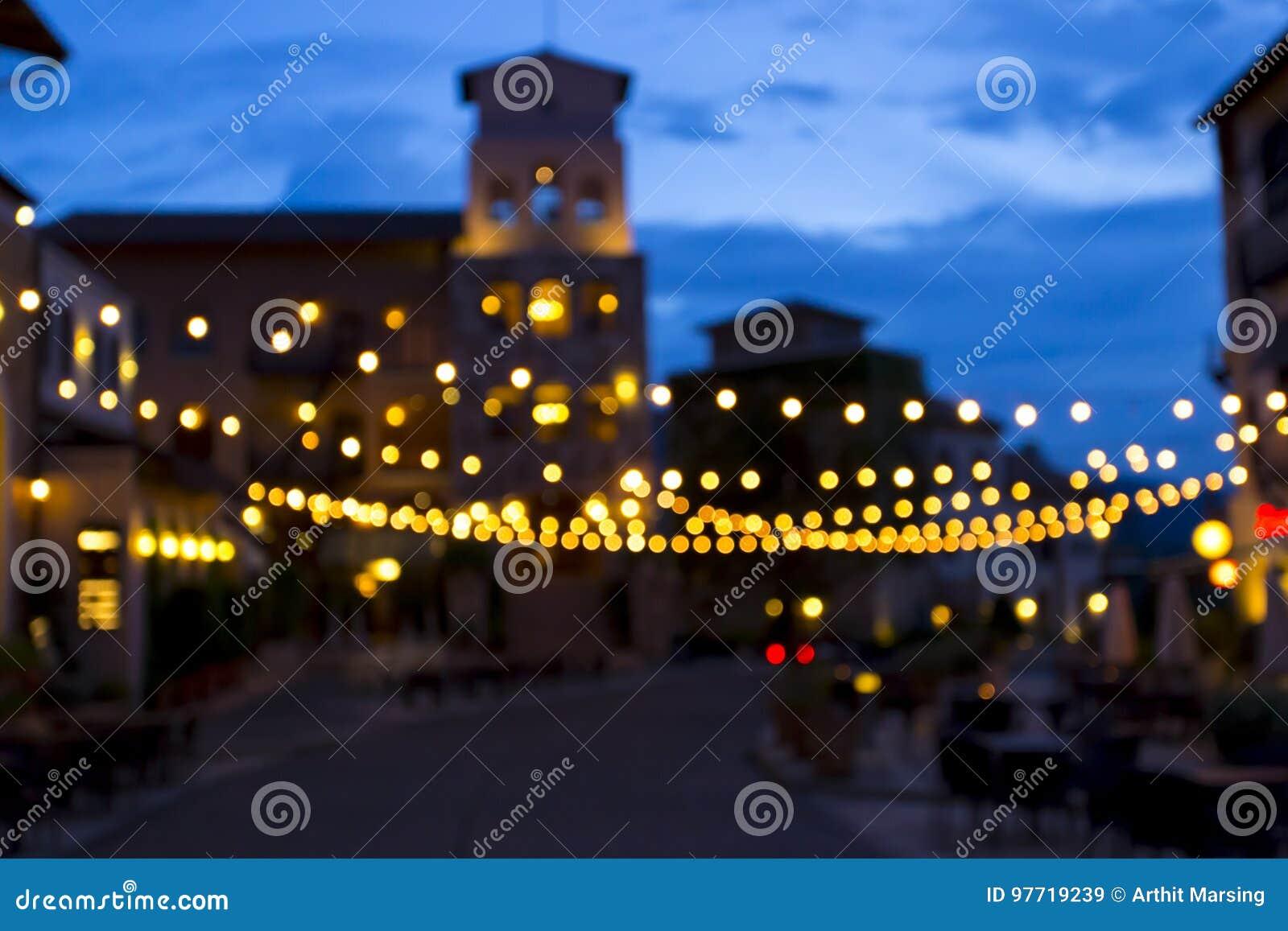 De Bokehachtergrond van beeld wordt gecreeerd van verfraait licht in stadsvierkant op avondtijd die Kan gebruik zijn als achtergr