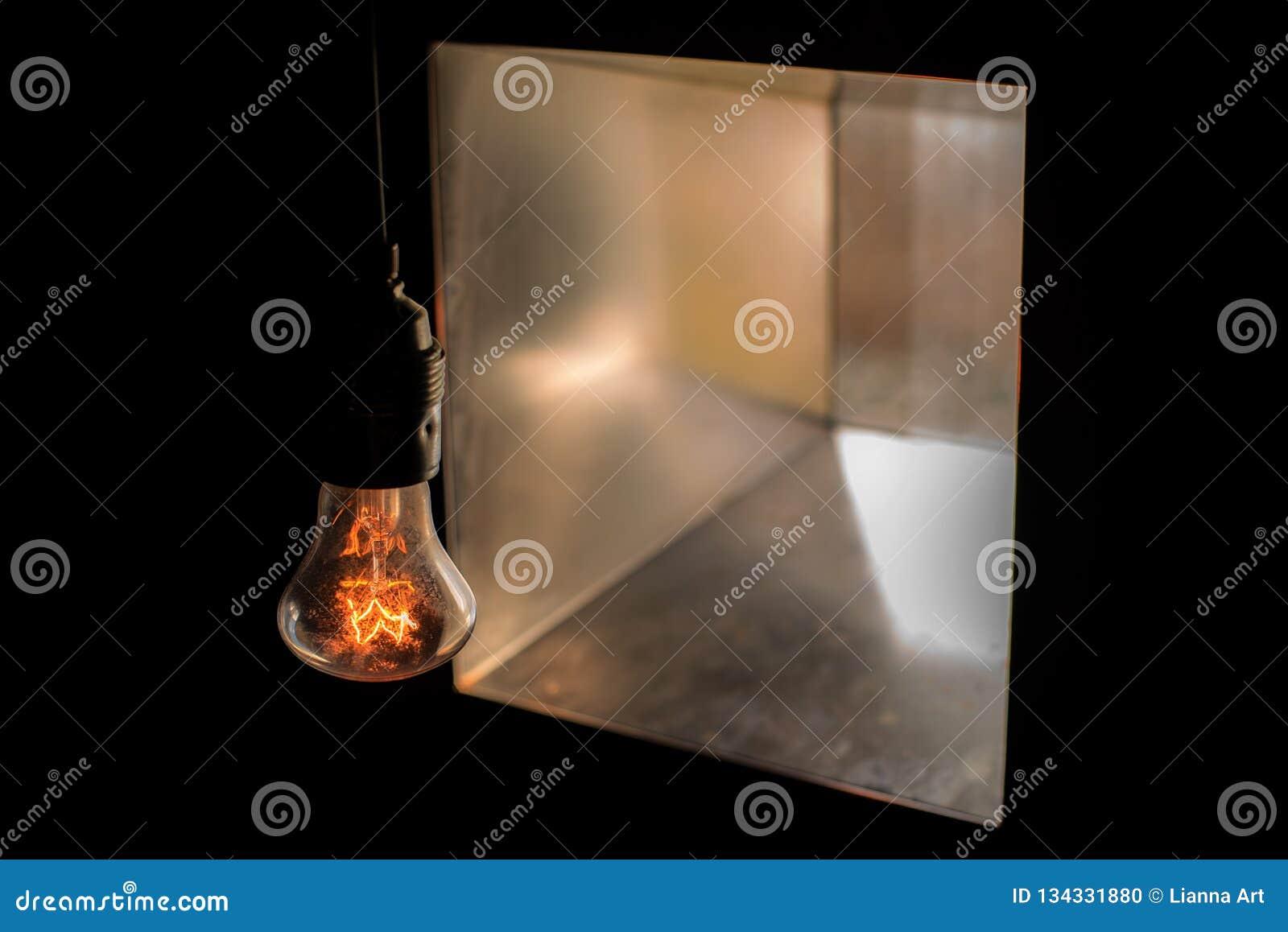 De bol van de gloedlamp zonder lampschaduw in dark tegengesteld aan een vierkant venster