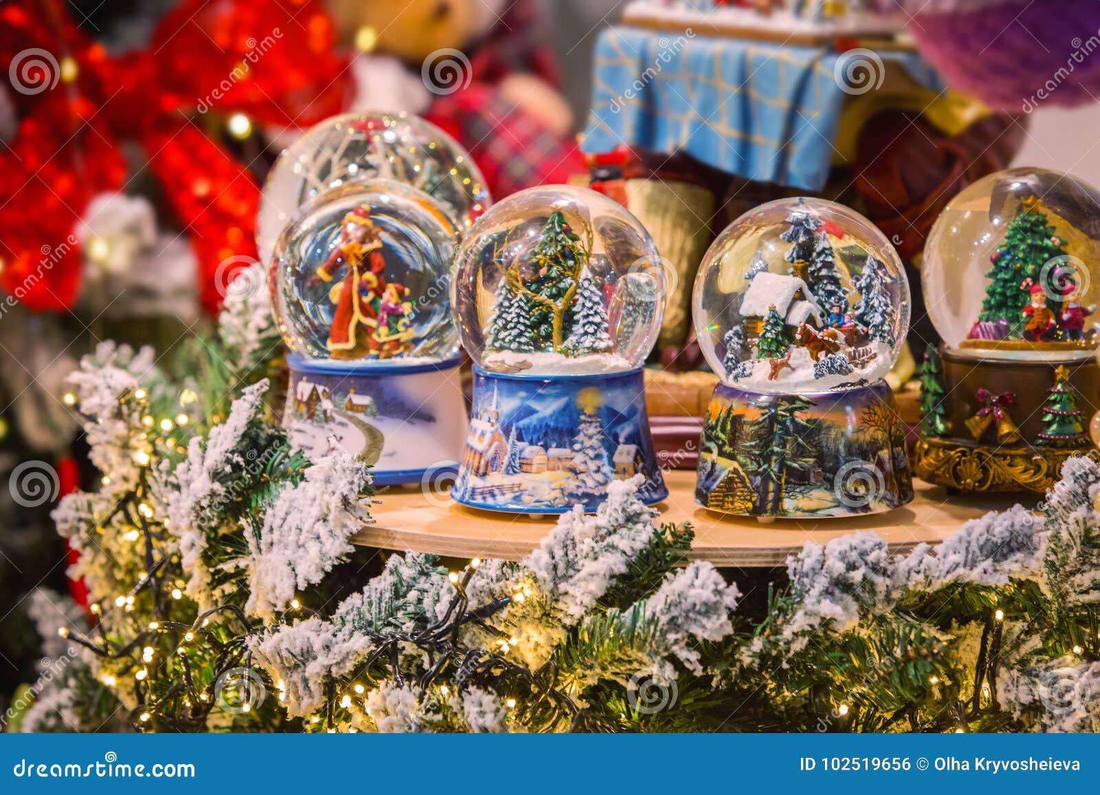 De bol van de de sneeuwbal van het Kerstmisglas met de nieuwe decoratie van het jaarspeelgoed